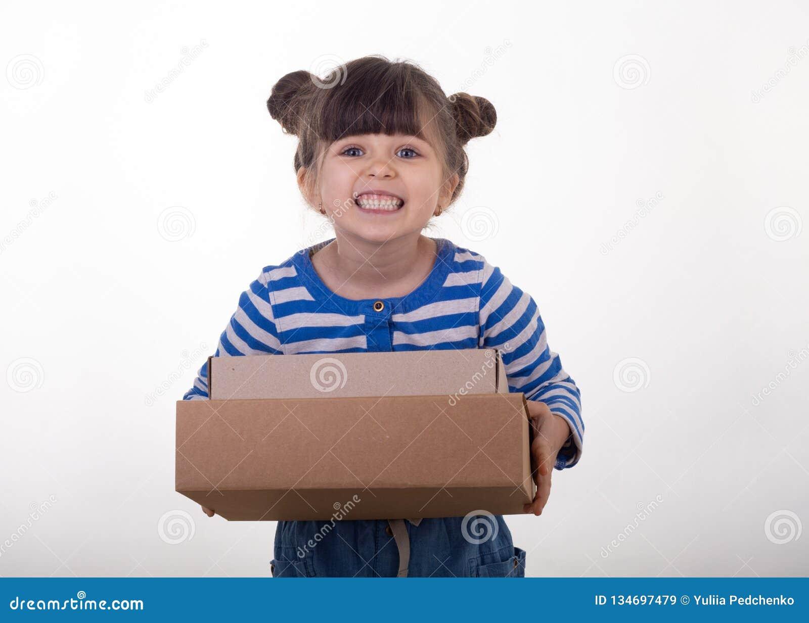 Εικόνα ενός ευτυχούς παιδιού που στέκεται με το κιβώτιο υπηρεσιών αποστολής δεμάτων που απομονώνεται πέρα από το άσπρο υπόβαθρο