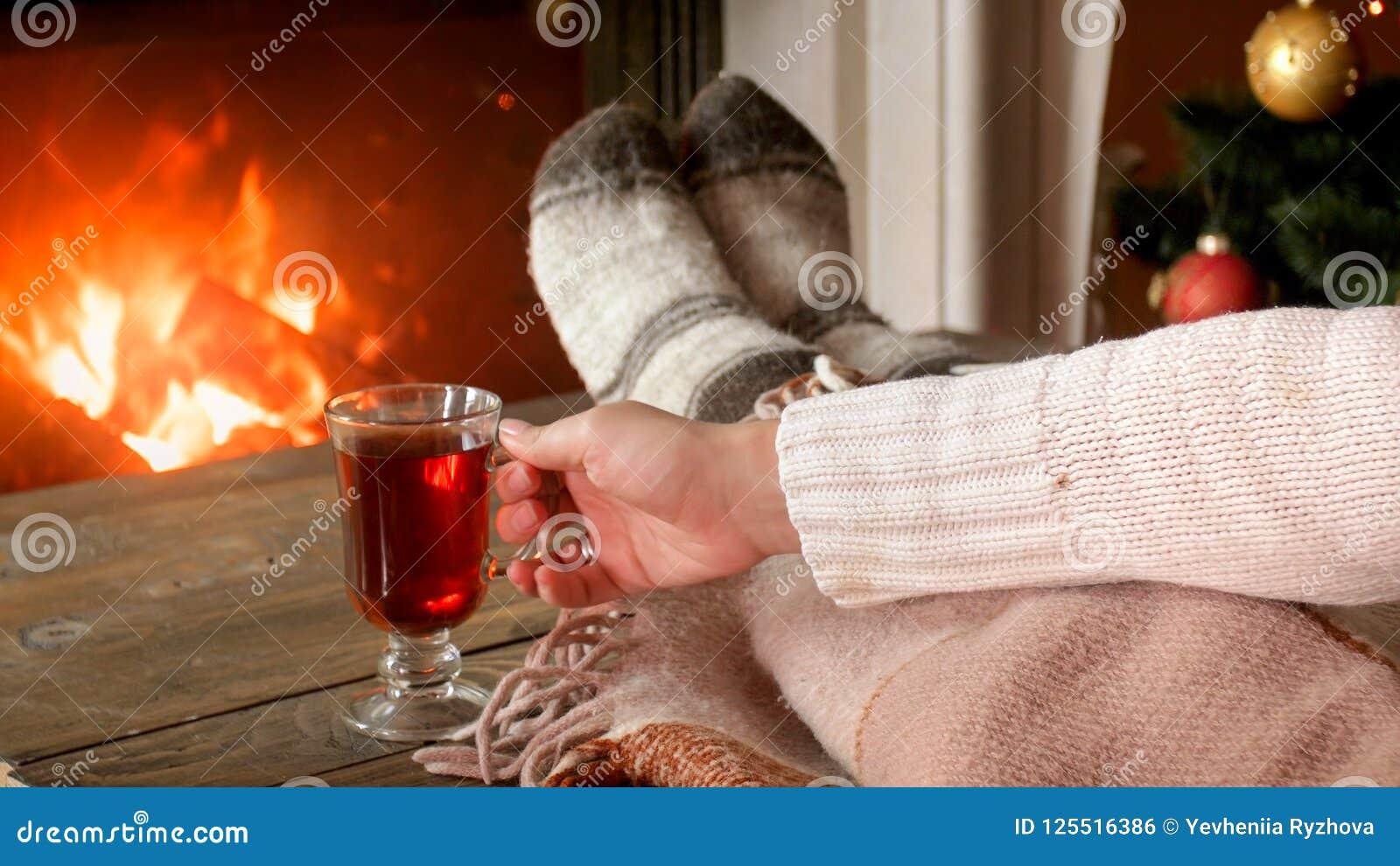 Εικόνα κινηματογραφήσεων σε πρώτο πλάνο της γυναίκας που πίνει το θερμαμένο κρασί στο καθιστικό Υ η εστία