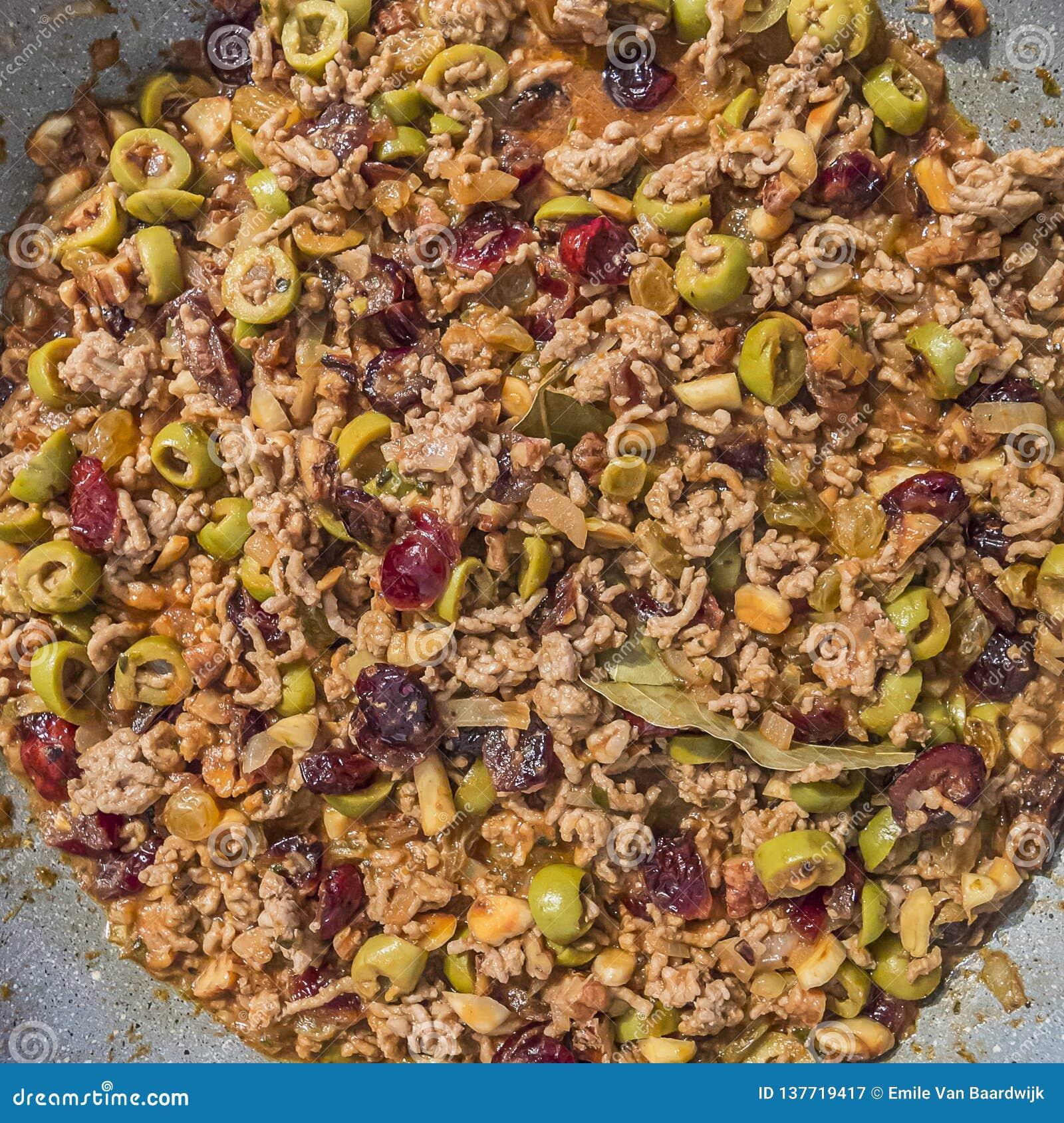 Εικόνα μιας πλήρωσης με το επίγειο κρέας, τις ελιές, τις σταφίδες, τα τα βακκίνια, τα ξύλα καρυδιάς, τα αμύγδαλα, το φύλλο κόλπων