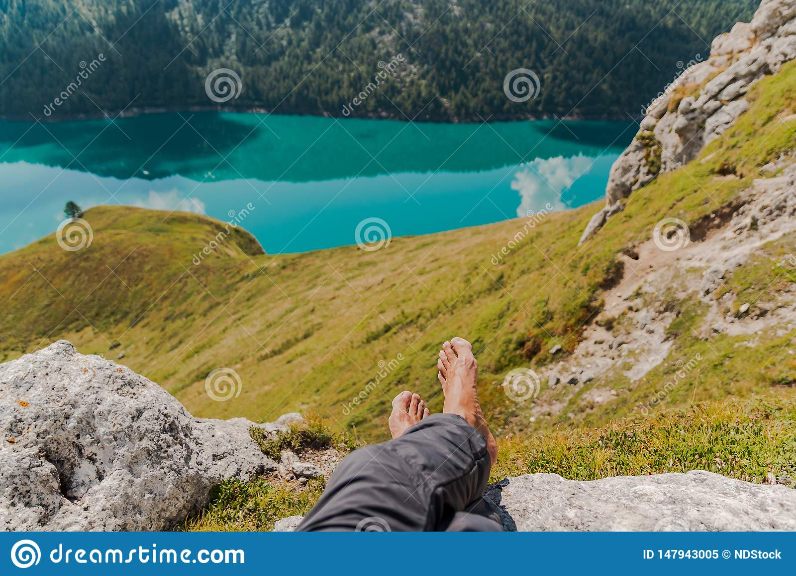 Εικόνα των αρσενικών ποδιών και των ποδιών με τα βουνά και της λίμνης Ritom ως υπόβαθρο