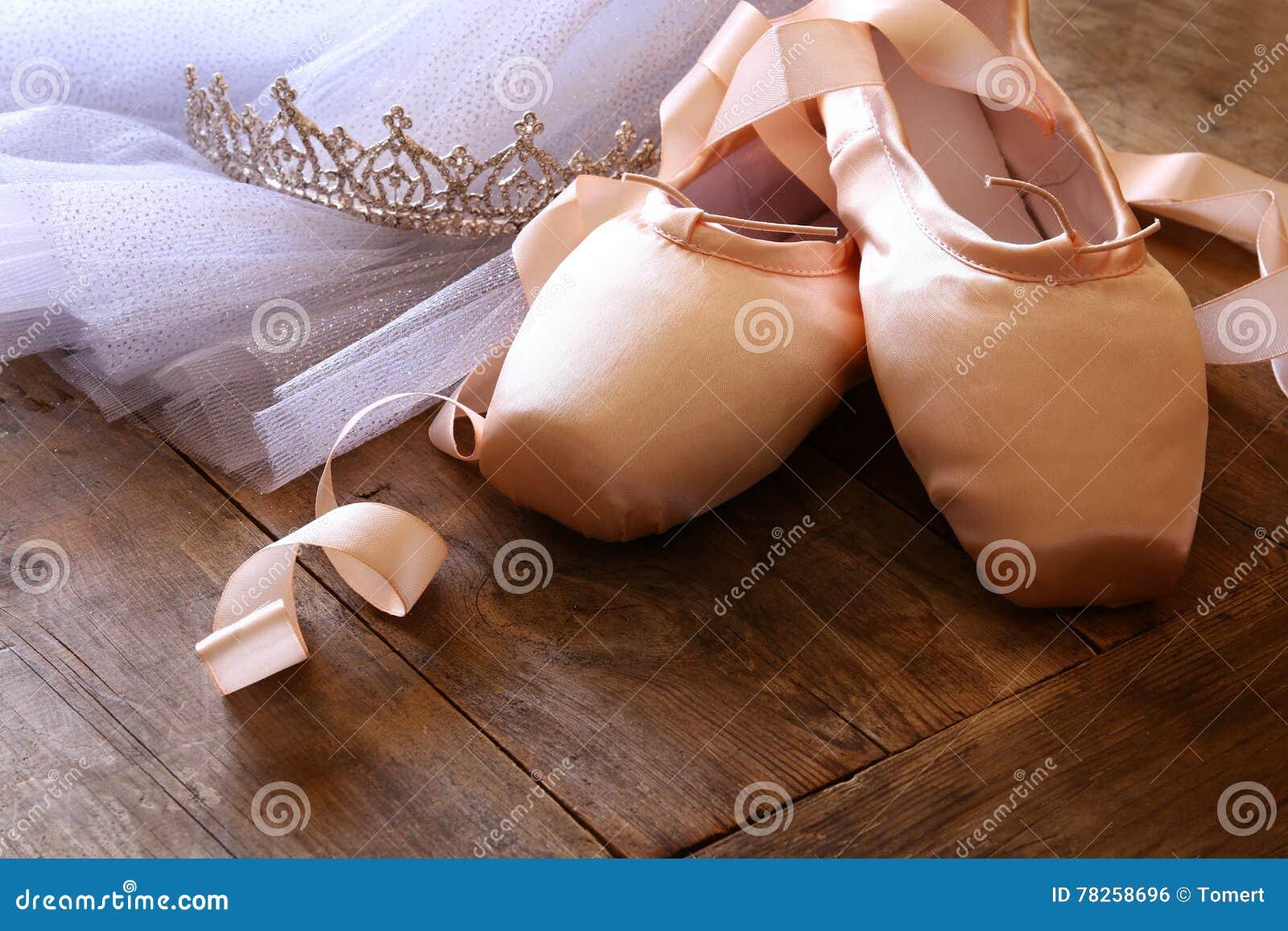 Εικόνα των παπουτσιών και του tutu μεταξιού pointe στο ξύλινο πάτωμα