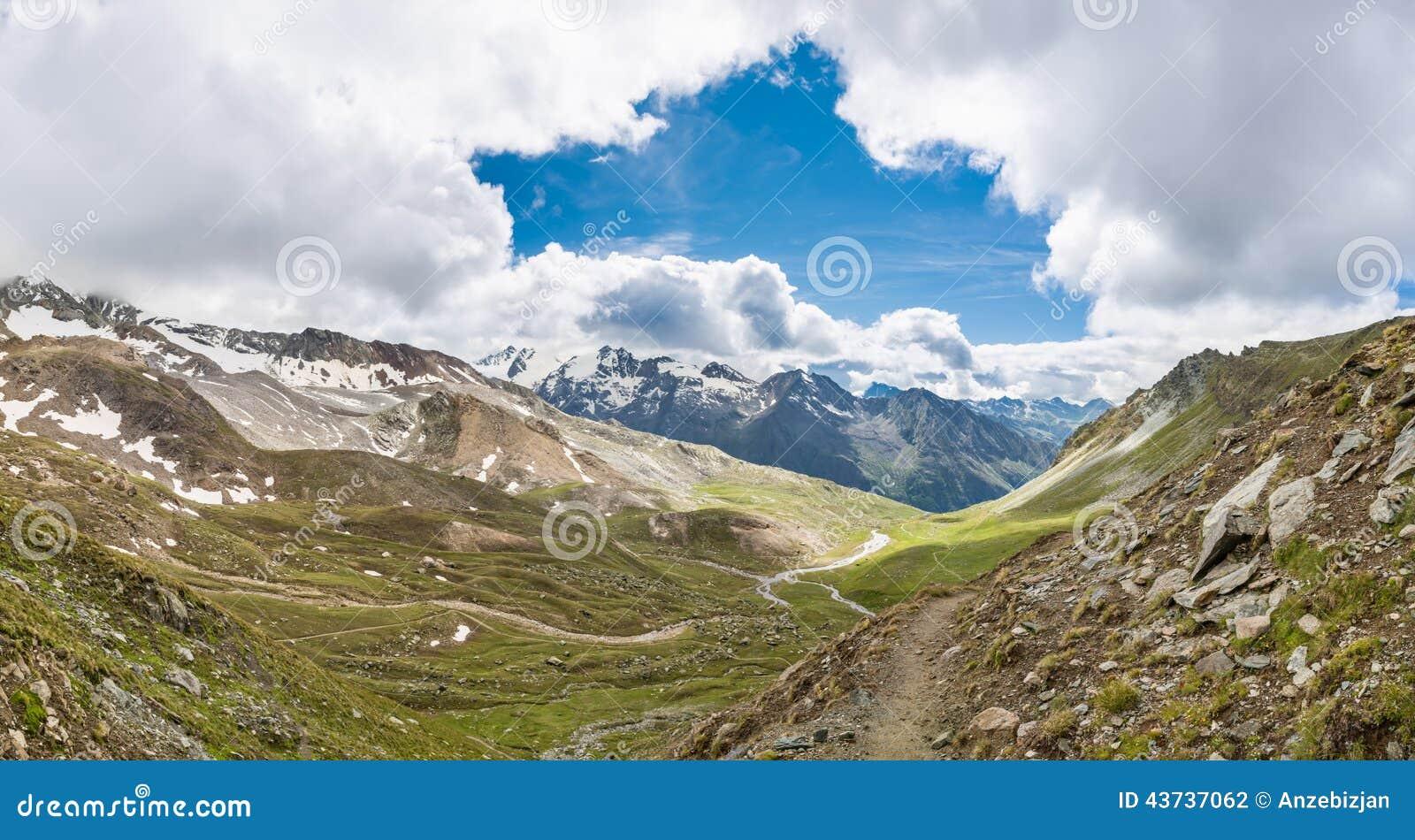 Ειδυλλιακή κοιλάδα βουνών με το άνοιγμα στον ουρανό