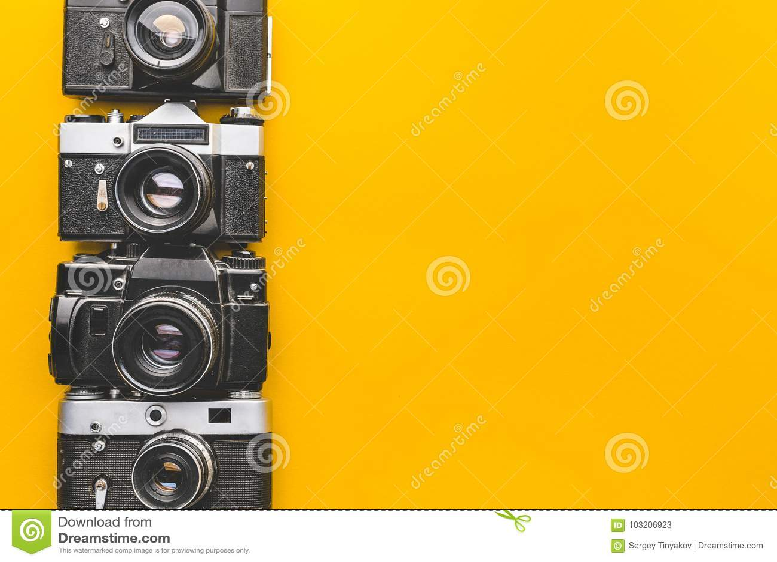 Εκλεκτής ποιότητας κάμερες ταινιών στην κίτρινη επιφάνεια υποβάθρου Αναδρομική έννοια τεχνολογίας δημιουργικότητας