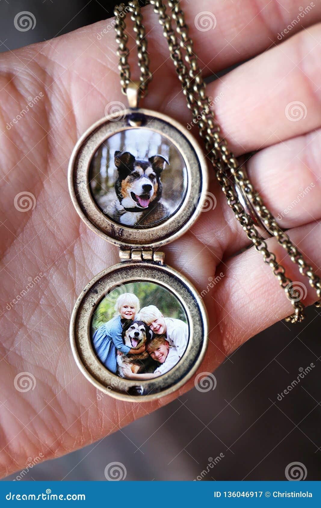 Εκμετάλλευση παλαιό Locket χεριών γυναίκας με τις φωτογραφίες των παιδιών και του σκυλιού της Pet μέσα