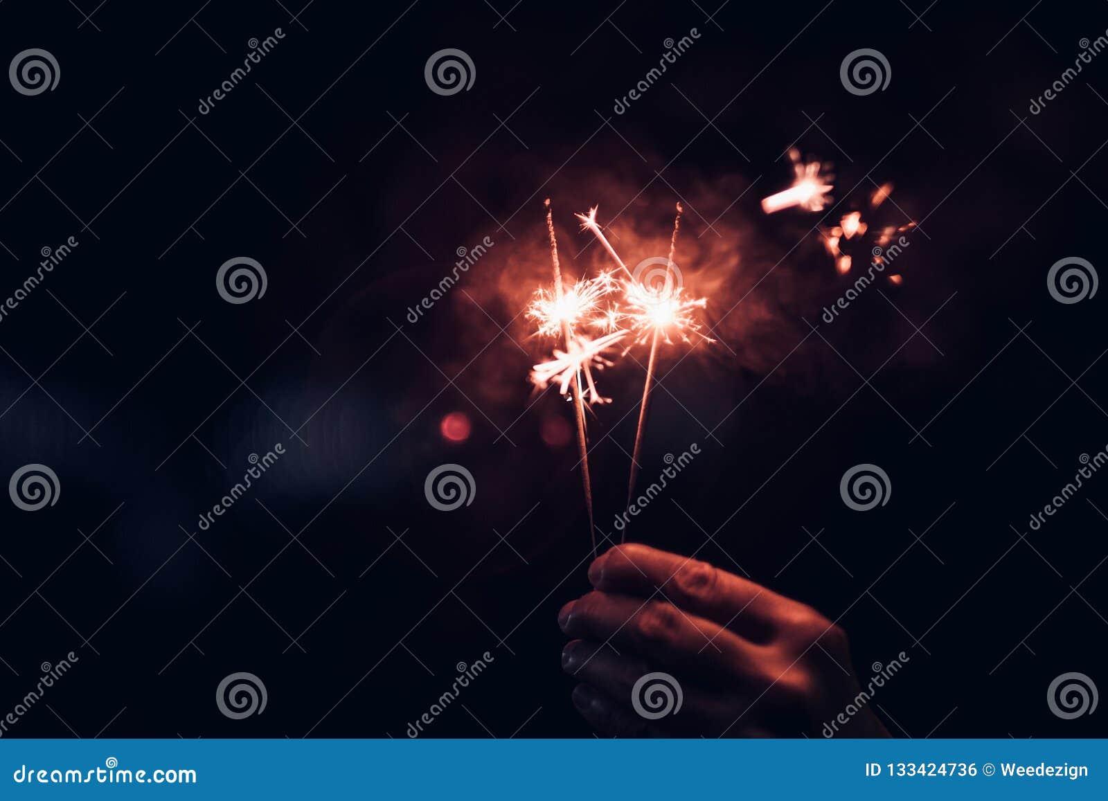 Εκμετάλλευση χεριών που καίει το φύσημα Sparkler σε ένα μαύρο υπόβαθρο bokeh