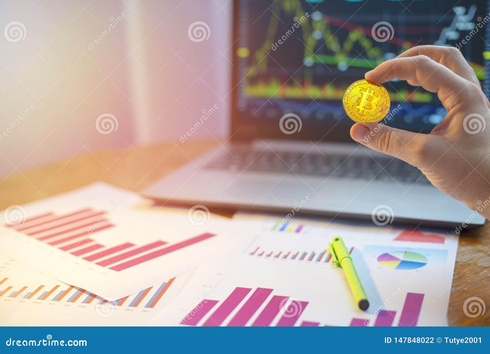Εκμετάλλευση χεριών bitcoin μπροστά από το lap-top και τα διαγράμματα στο γραφείο