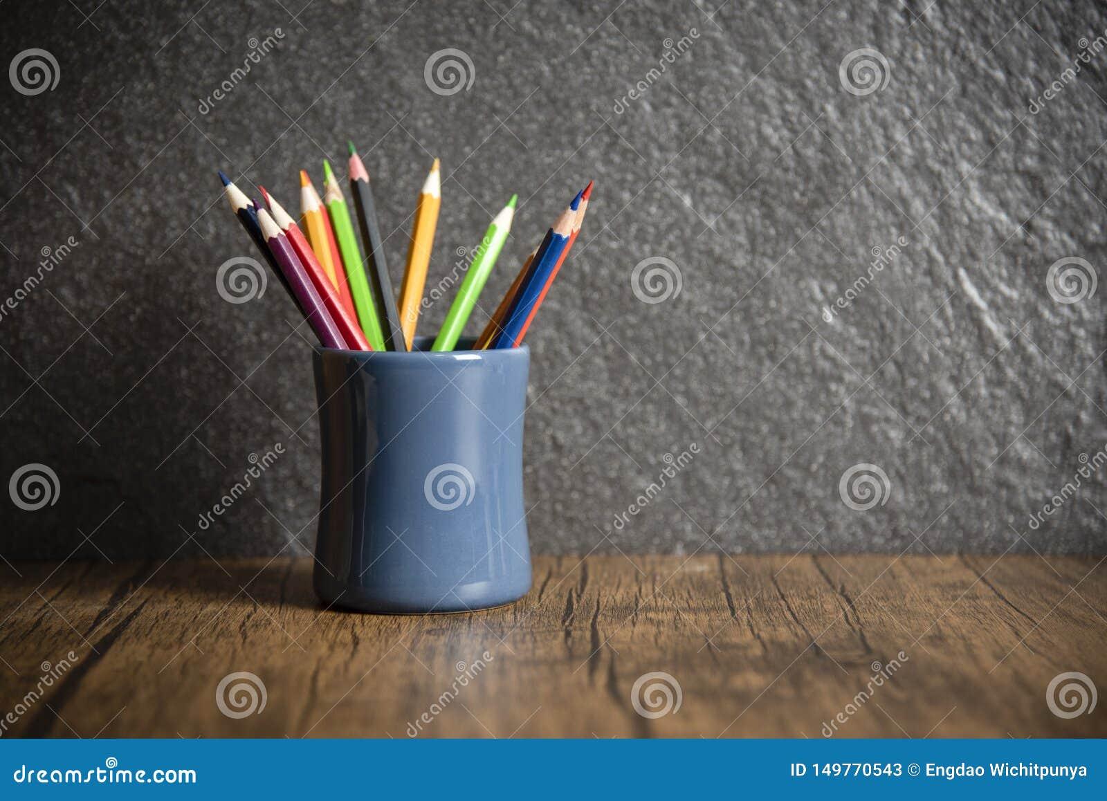 Εκπαίδευση και πίσω στη σχολική έννοια με τα μολύβια ζωηρόχρωμα σε μια περίπτωση μολυβιών στο σκοτεινό υπόβαθρο - ξύλινο κραγιόνι