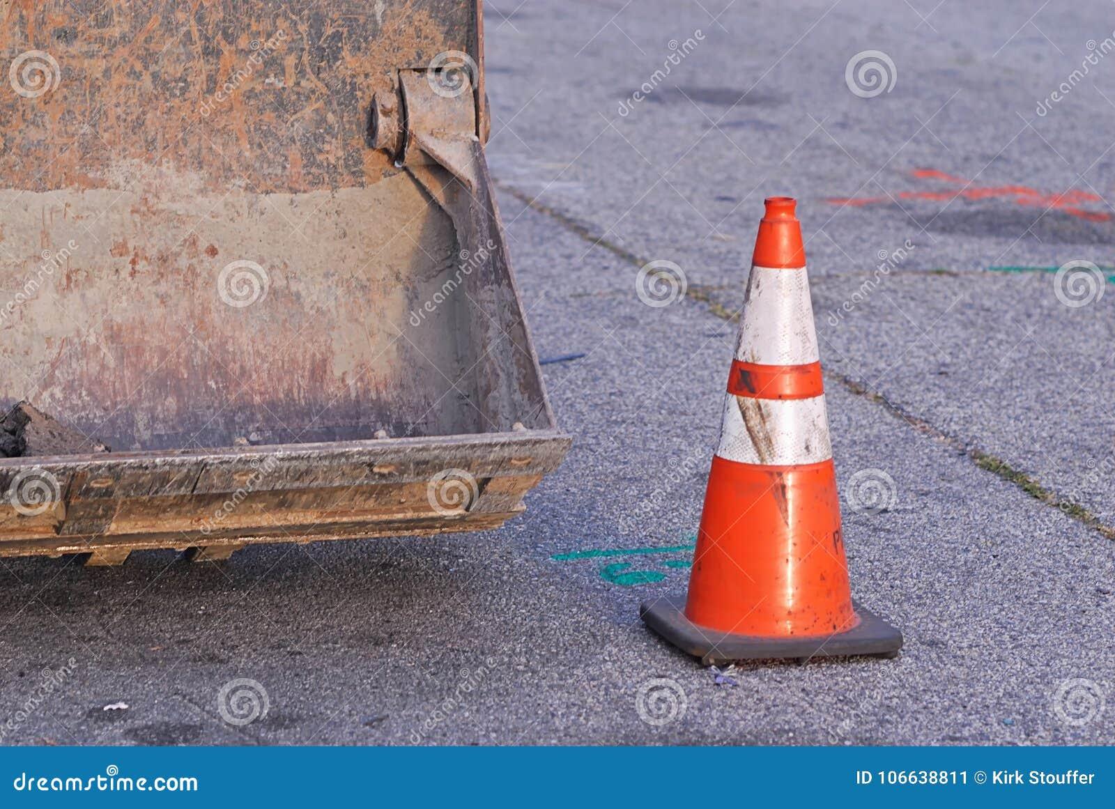 Εκσακαφέας με το ριγωτό πορτοκαλή κώνο κυκλοφορίας σε κάποια οδό