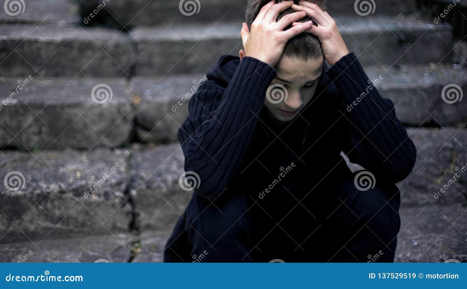 Εκφοβισμένη μόνη συνεδρίαση αγοριών στα παλαιά ραγισμένα βήματα, ηχώ του πολέμου, θλίψη στη ζωή