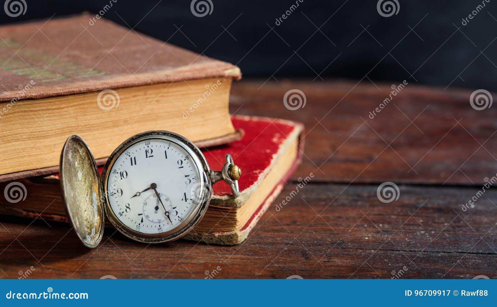 Εκλεκτής ποιότητας βιβλία και ρολόι τσεπών στο σκοτεινό υπόβαθρο