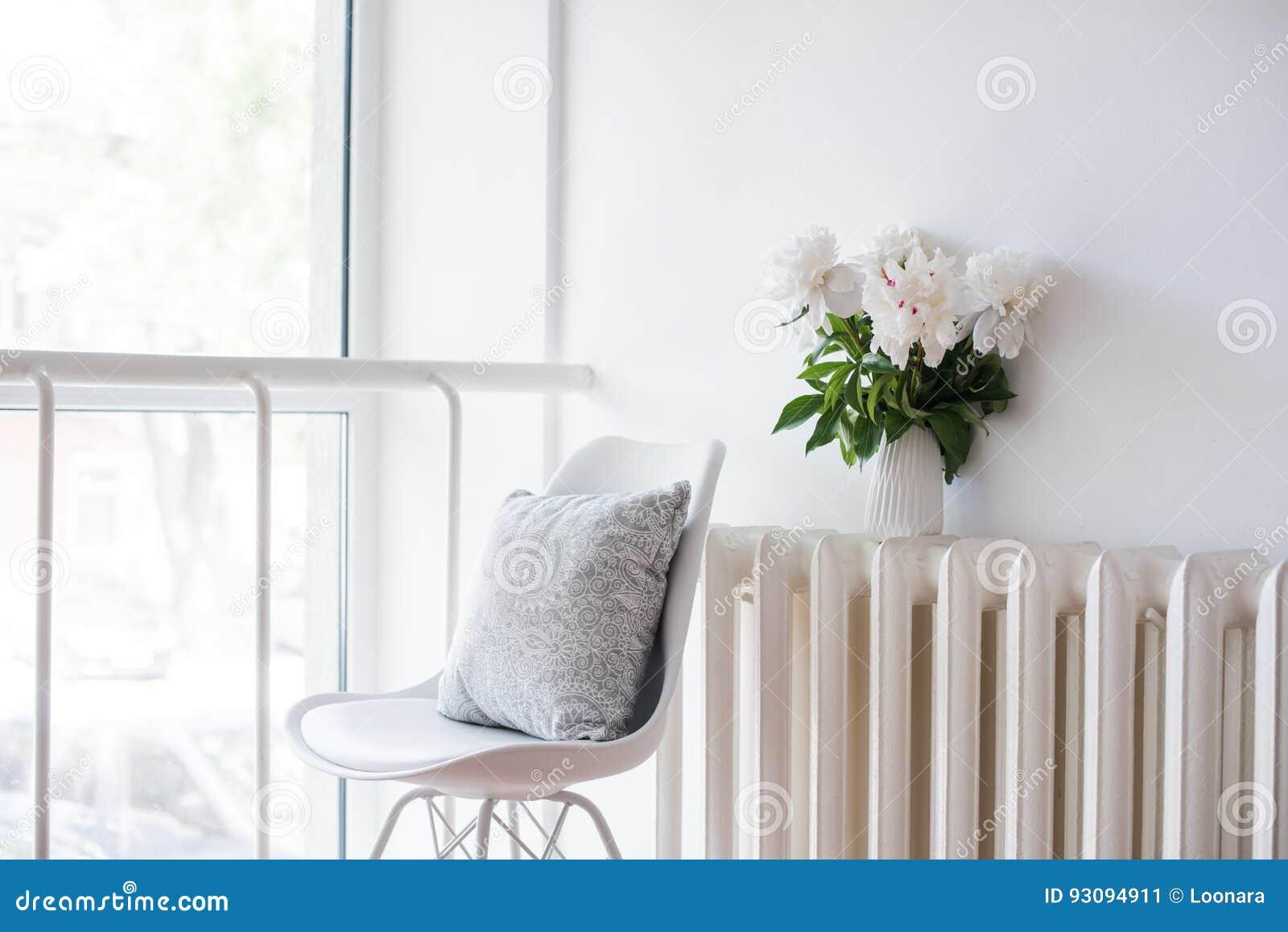 Εκλεκτής ποιότητας εγχώρια διακόσμηση, φρέσκες peonies και καρέκλα σχεδιαστών με