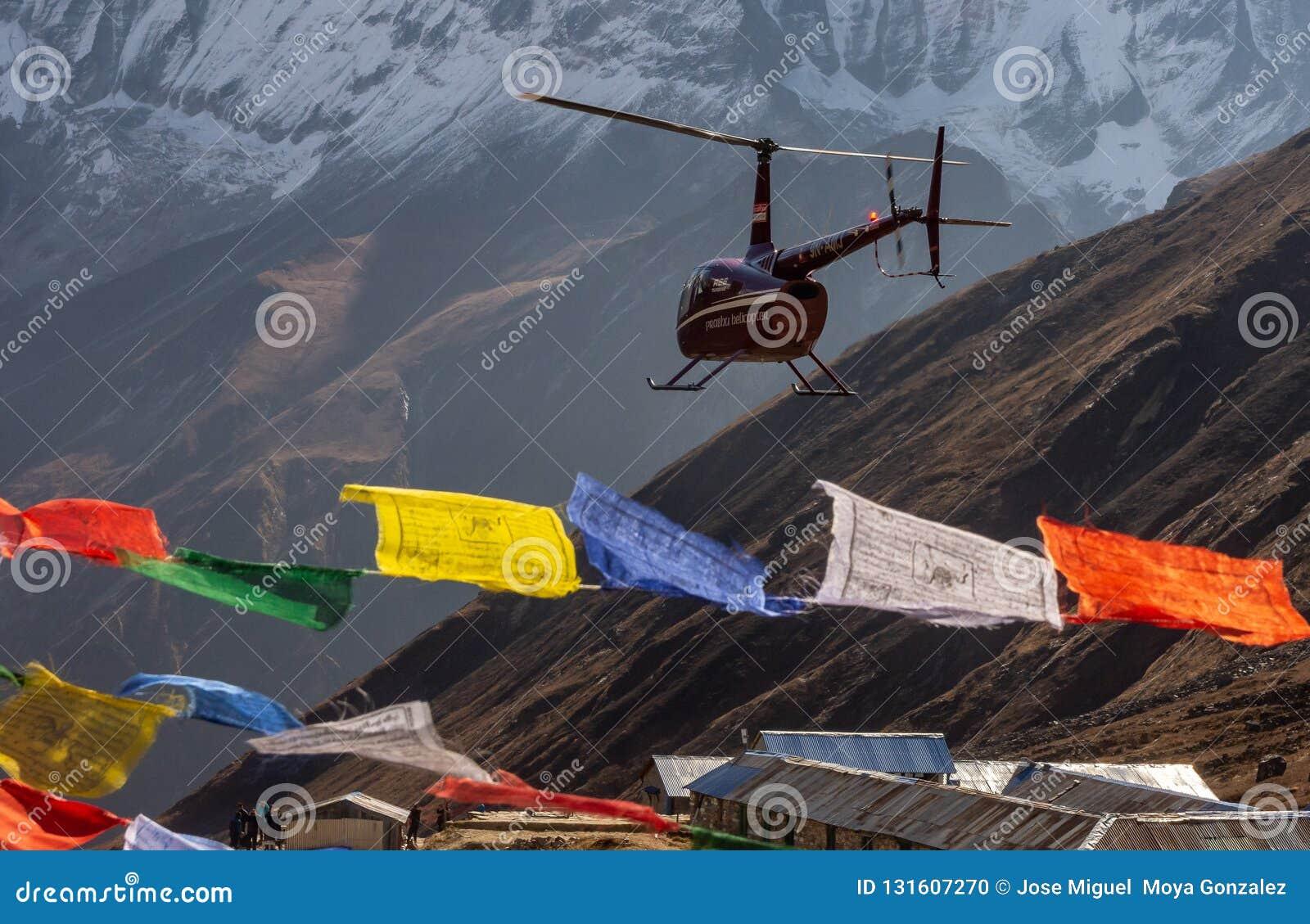 Ελικόπτερο και ζωηρόχρωμες θιβετιανές σημαίες προσευχής στο στρατόπεδο βάσεων Annapurna, Ιμαλάια