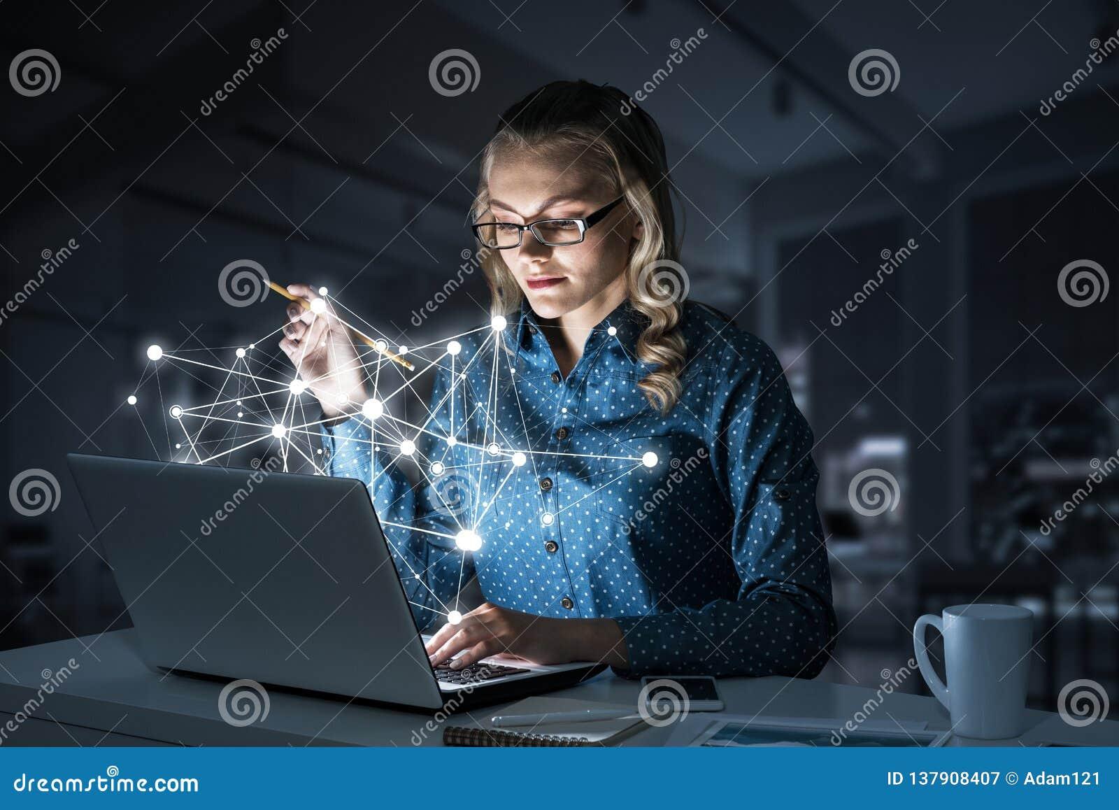 Ελκυστικά ξανθά φορώντας γυαλιά στο σκοτεινό γραφείο που χρησιμοποιεί το lap-top Μικτά μέσα