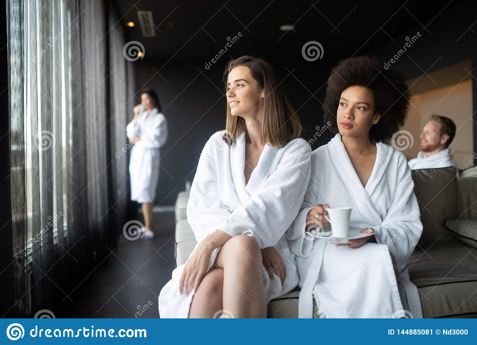 Ελκυστικές ευτυχείς νέες γυναίκες που πίνουν τον καφέ στο κέντρο SPA