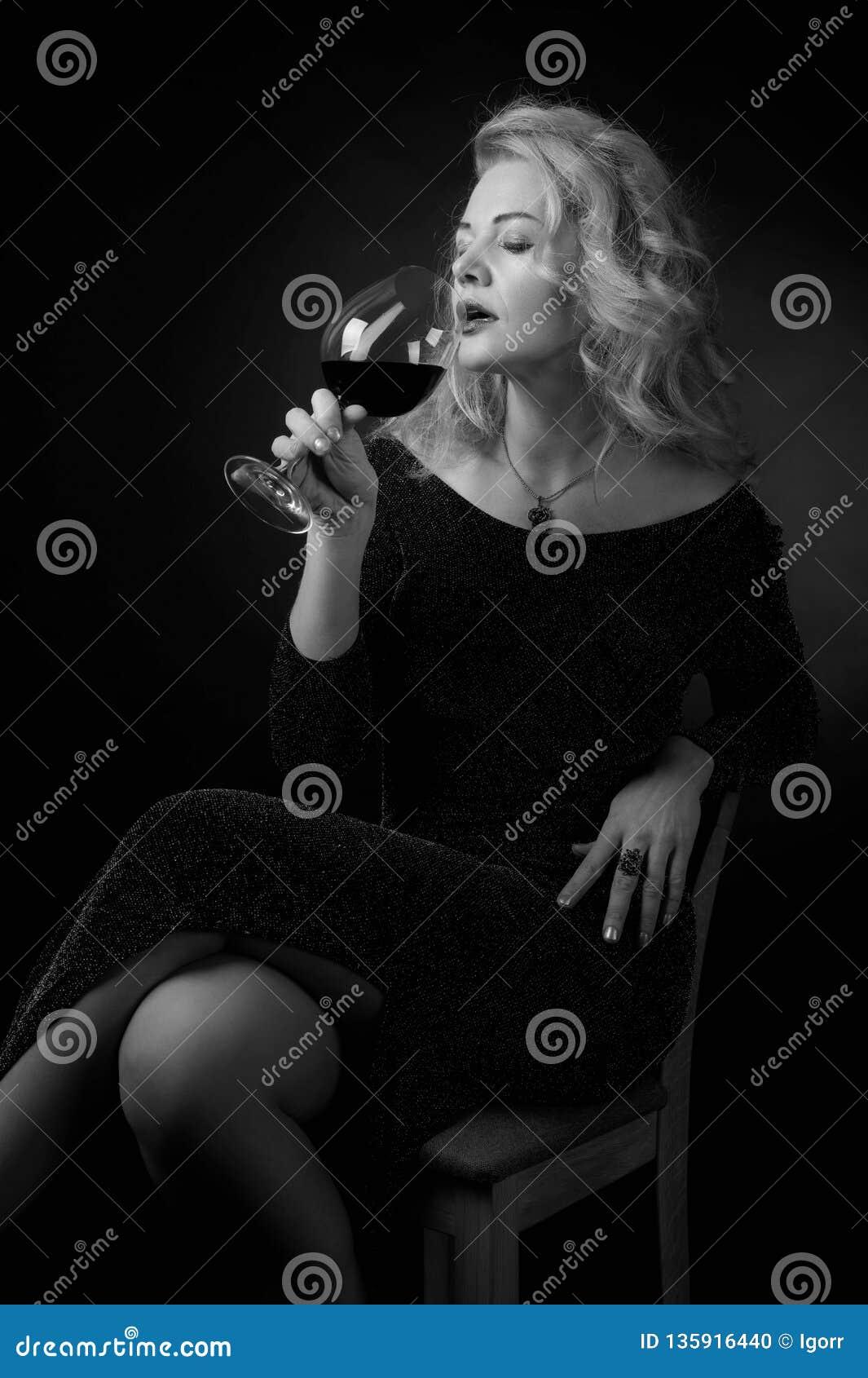 Ελκυστική γυναίκα Μεσαίωνα στο μαύρο φόρεμα βραδιού με το ποτήρι του κόκκινου κρασιού