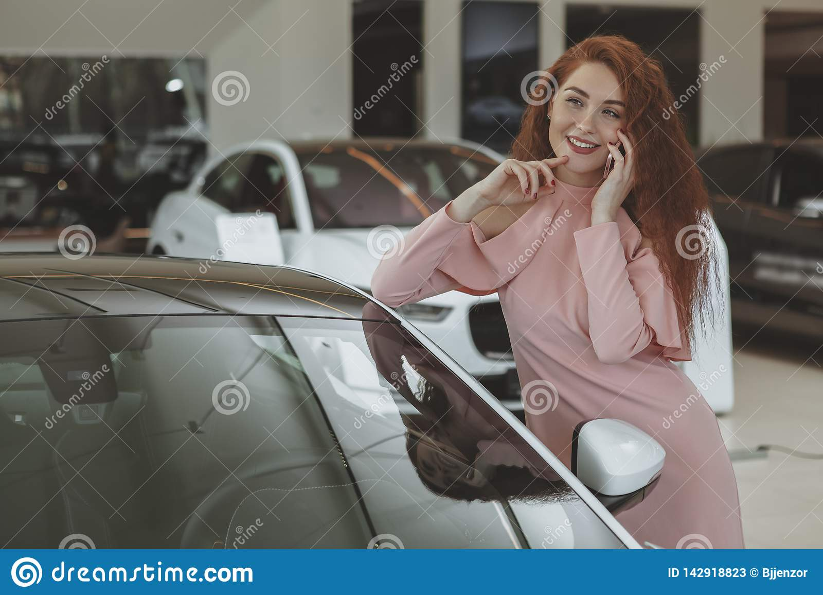 Ελκυστική γυναίκα που χρησιμοποιεί το έξυπνο τηλέφωνό της bying το νέο αυτοκίνητο