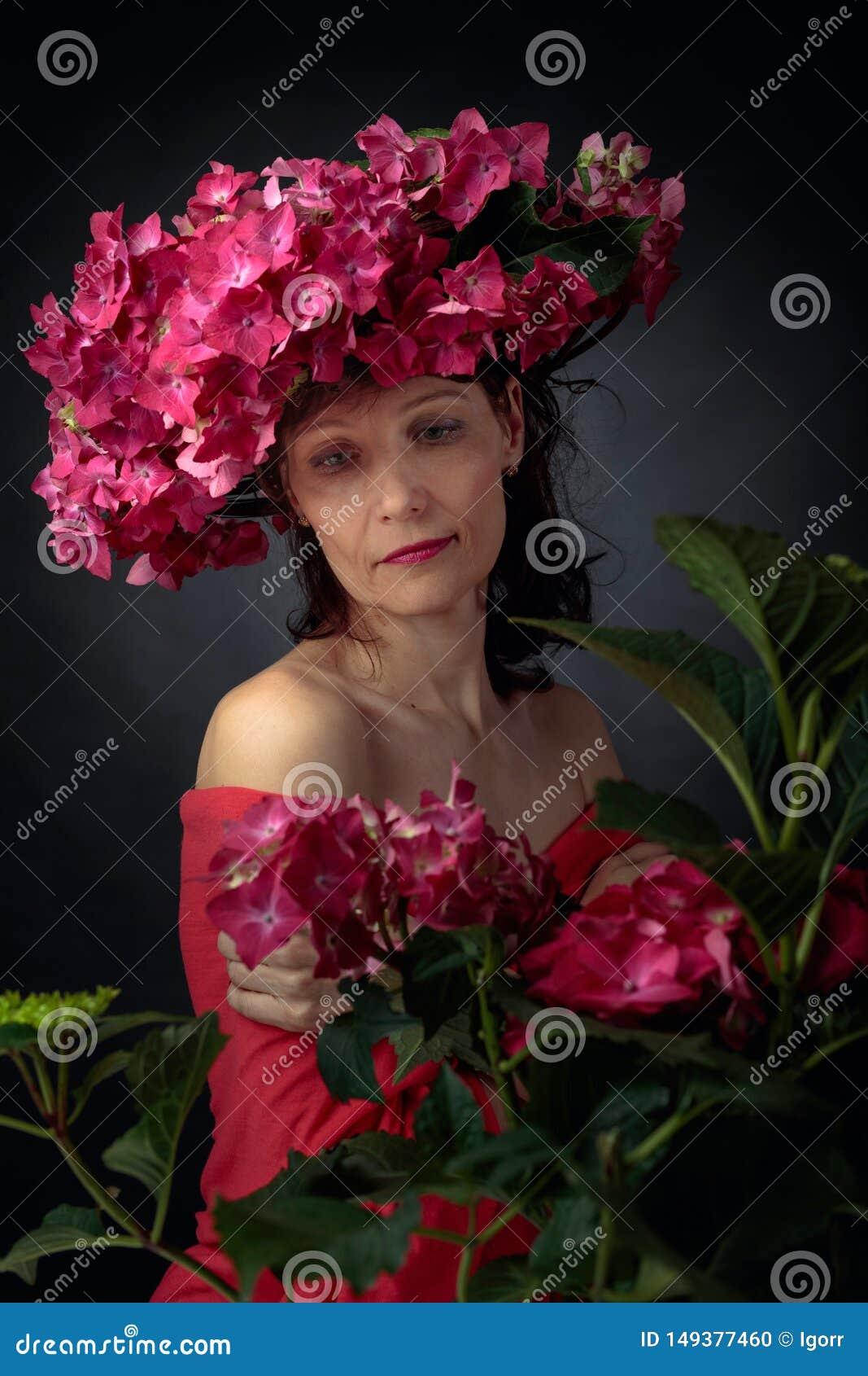 Ελκυστική γυναίκα στο στεφάνι με τα άνθη hydrangea κοραλλιών