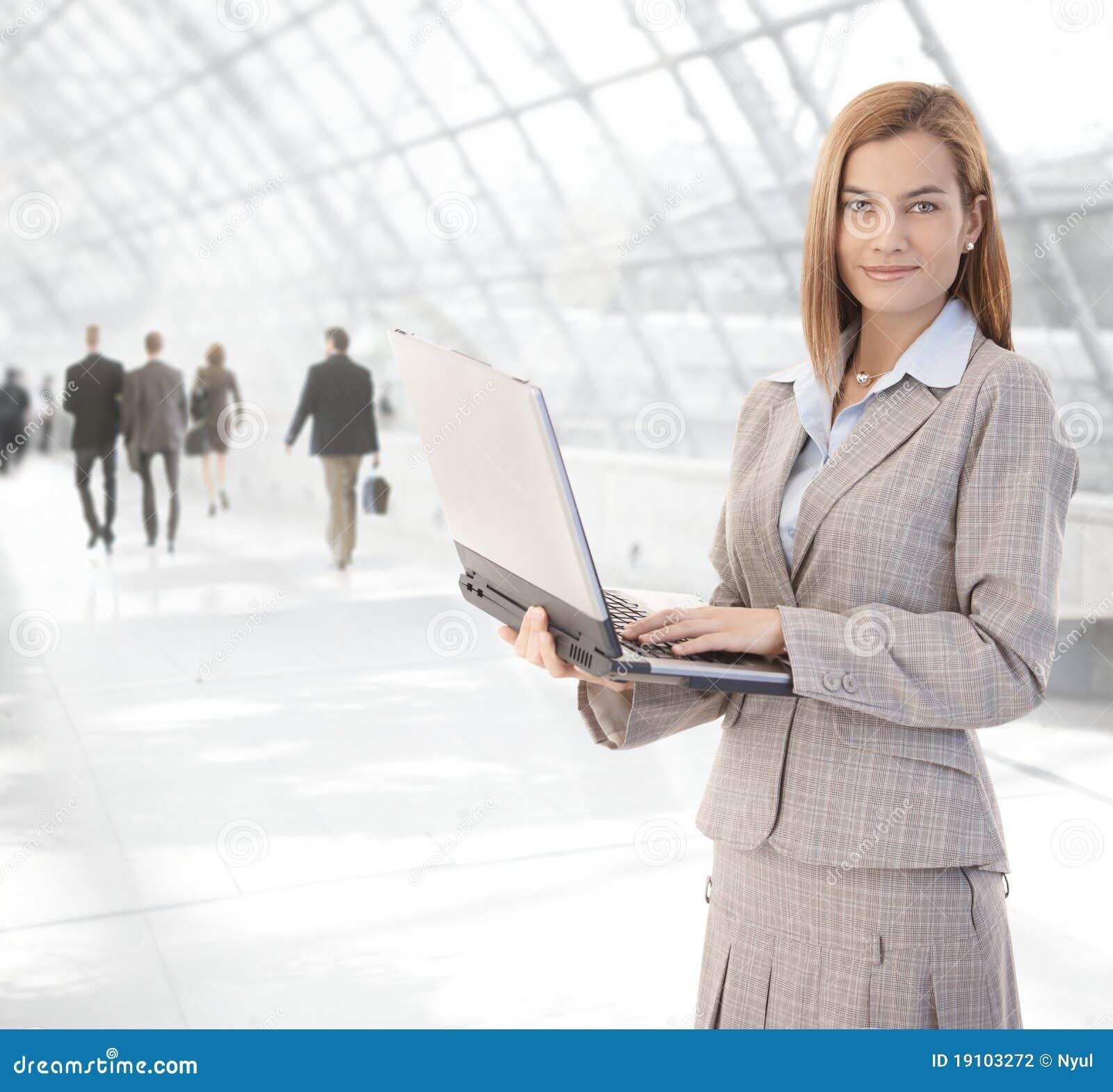 Ελκυστική επιχειρηματίας που χρησιμοποιεί το lap-top στη μετάβαση