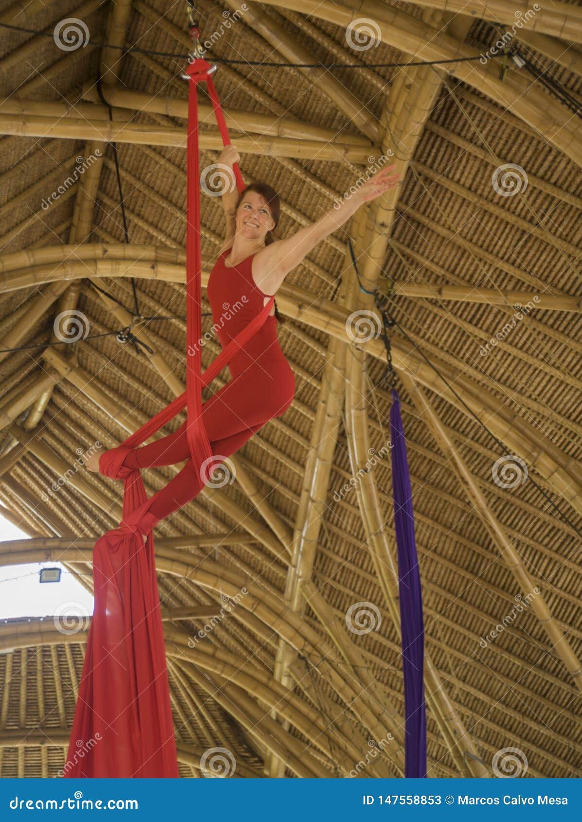 Ελκυστική και αθλητική ένωση γυναικών aerialist από το ύφασμα μεταξιού που κάνει την εναέρια κατάρτιση χορού workout ευτυχή στην