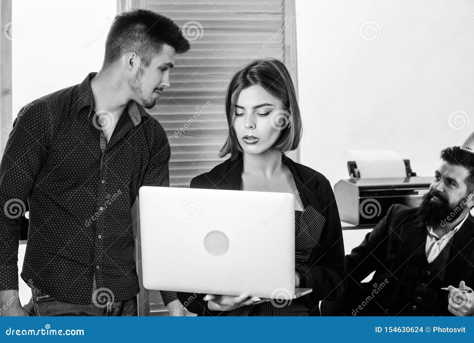 Ελκυστική κυρία γυναικών που συνεργάζεται με τους συναδέλφους ανδρών Συλλογική έννοια γραφείων Οι συνάδελφοι επικοινωνούν την επί