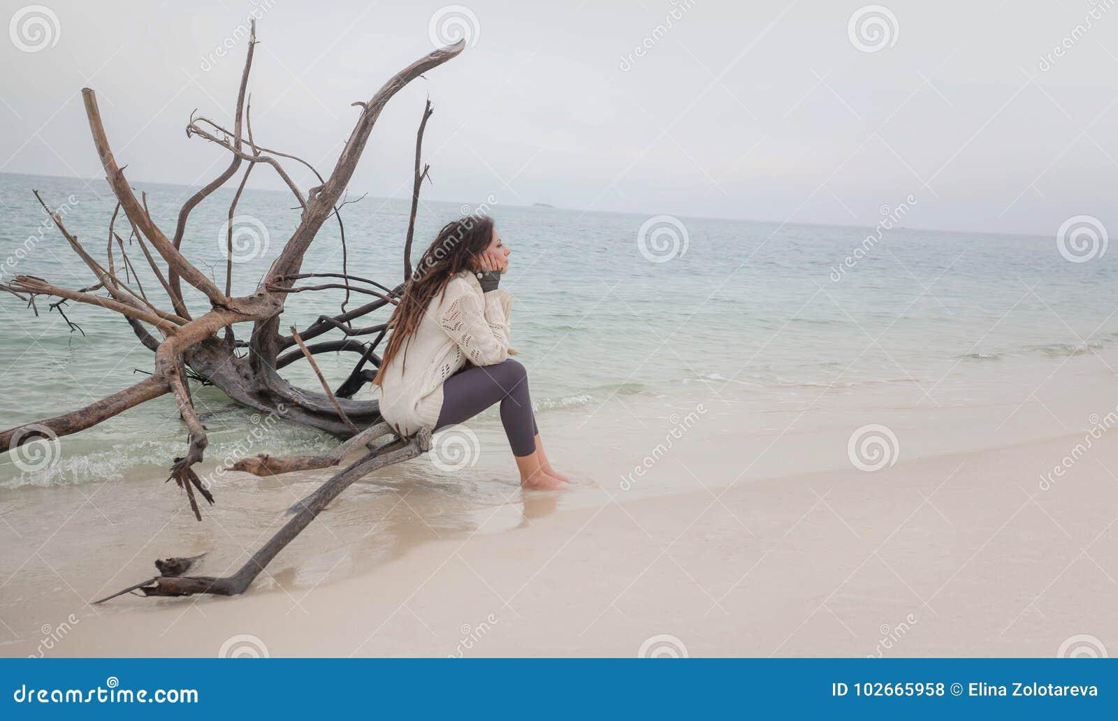 Ελκυστική νέα γυναίκα στη συνεδρίαση πουλόβερ στην παραλία