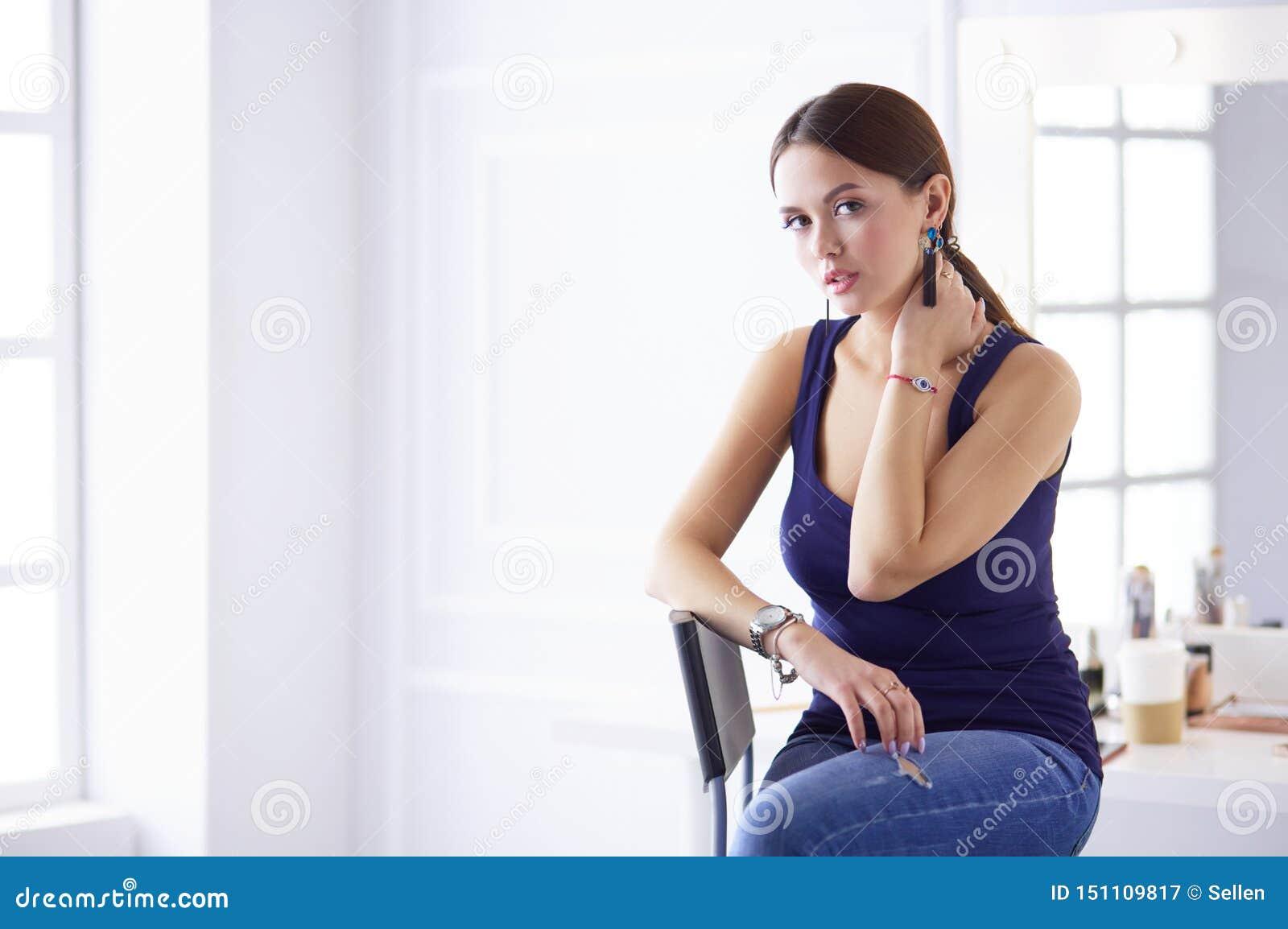 Ελκυστική συνεδρίαση γυναικών στην καρέκλα στο σαλόνι