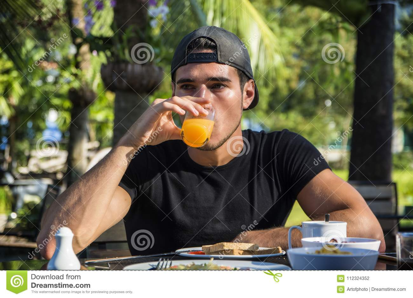 Ελκυστικός νεαρός άνδρας που τρώει το πρόγευμα