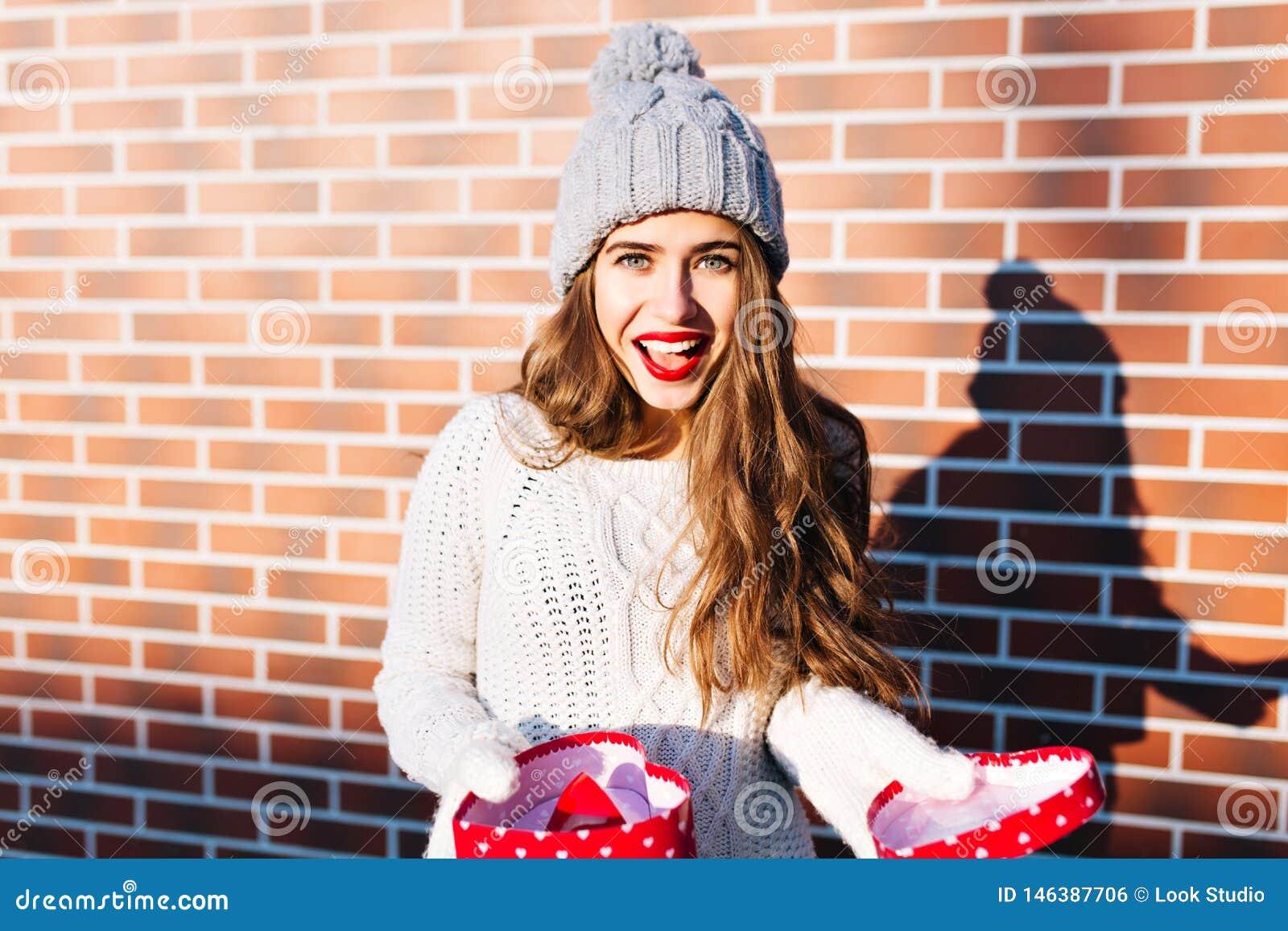 Ελκυστικό κορίτσι με μακρυμάλλη στο πλεκτό καπέλο με το ανοικτό παρόν στο υπόβαθρο τοίχων έξω Φορά το θερμό άσπρο πουλόβερ