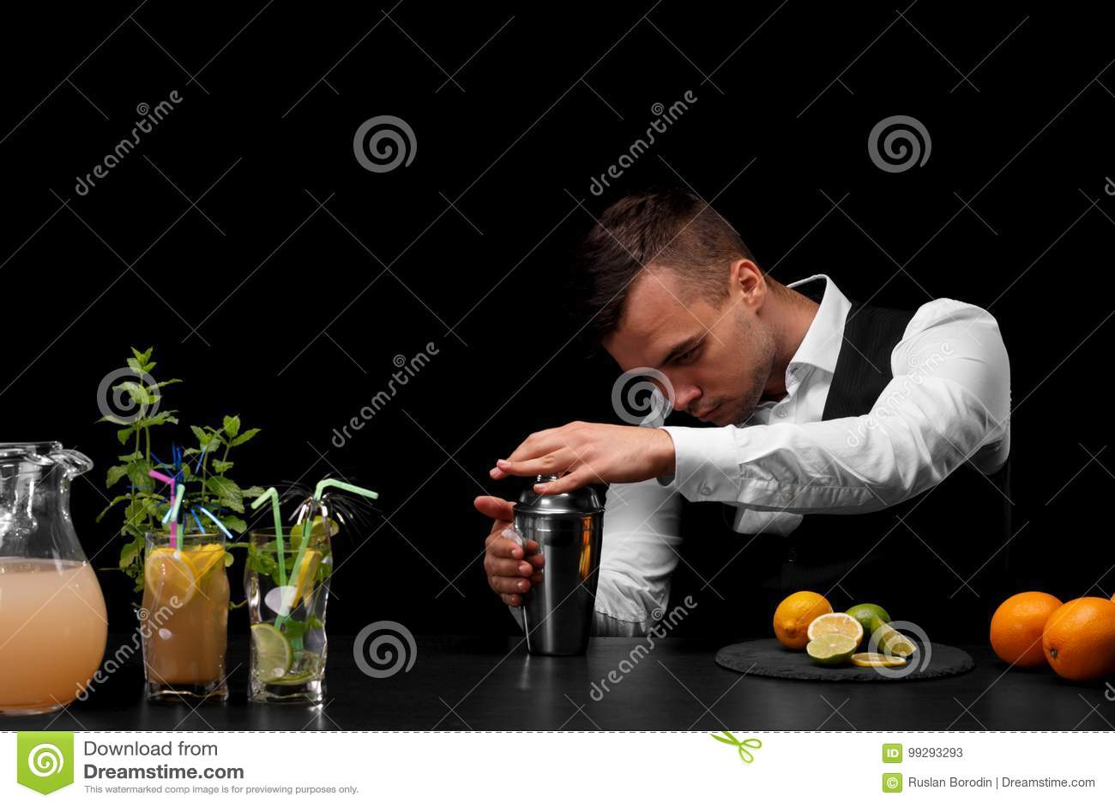Ελκυστικό bartender σκουπίζει έναν δονητή, ένας μετρητής φραγμών με τα κοκτέιλ, τους ασβέστες, το λεμόνι και τα πορτοκάλια σε ένα