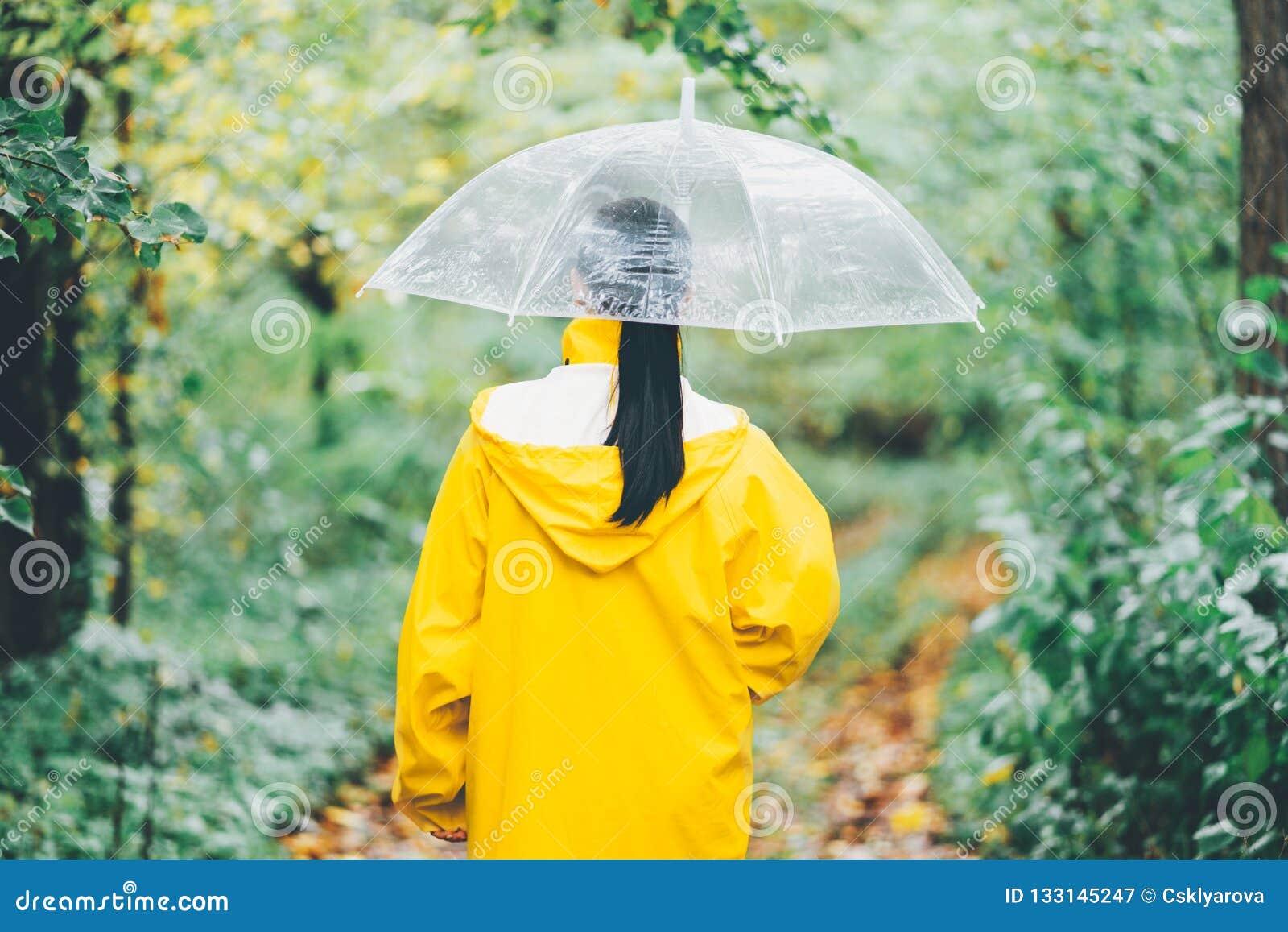 Ελκυστικό unrecognizable νέο κορίτσι στο κίτρινο αδιάβροχο που περπατά στο πάρκο με τη διαφανή ομπρέλα, ημέρα φθινοπώρου υποστηρί