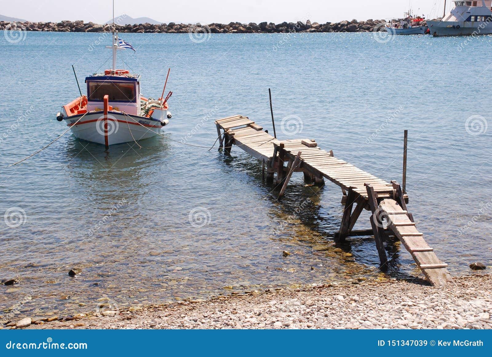 Ελληνικό αλιευτικό σκάφος που δένεται σε έναν ξεχαρβαλωμένο παλαιό λιμενοβραχίονα
