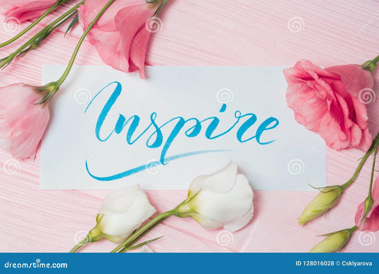 Εμπνεύστε το κείμενο Πηγή της κινητήριας λέξης εγγραφής στον άσπρο καμβά με το μπλε μελάνι Πλαίσιο eustoma λουλουδιών στο ρόδινο