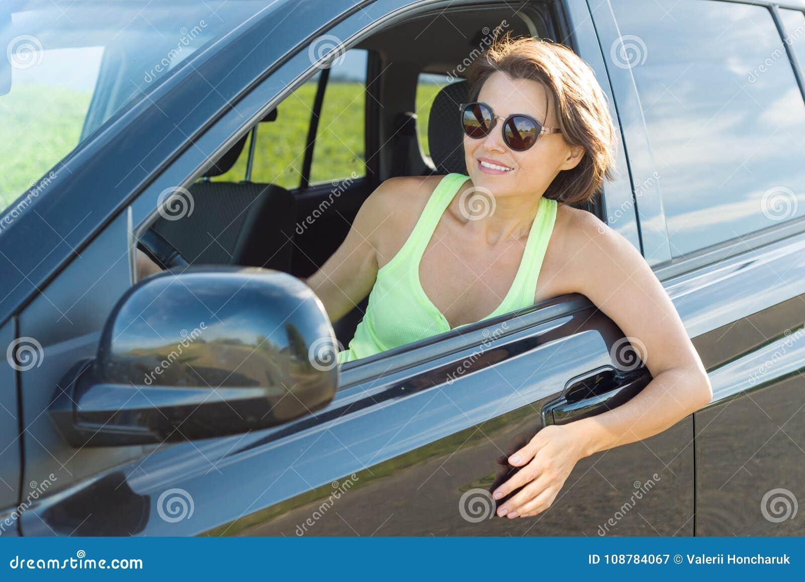 Ενήλικη ελκυστική συνεδρίαση γυναικών στο αυτοκίνητο - θερινό πορτρέτο υπαίθριο