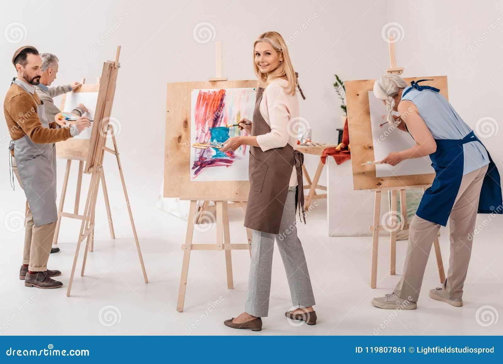 ενήλικοι άνδρες και γυναίκες σπουδαστές στις ποδιές που χρωματίζουν μαζί easels