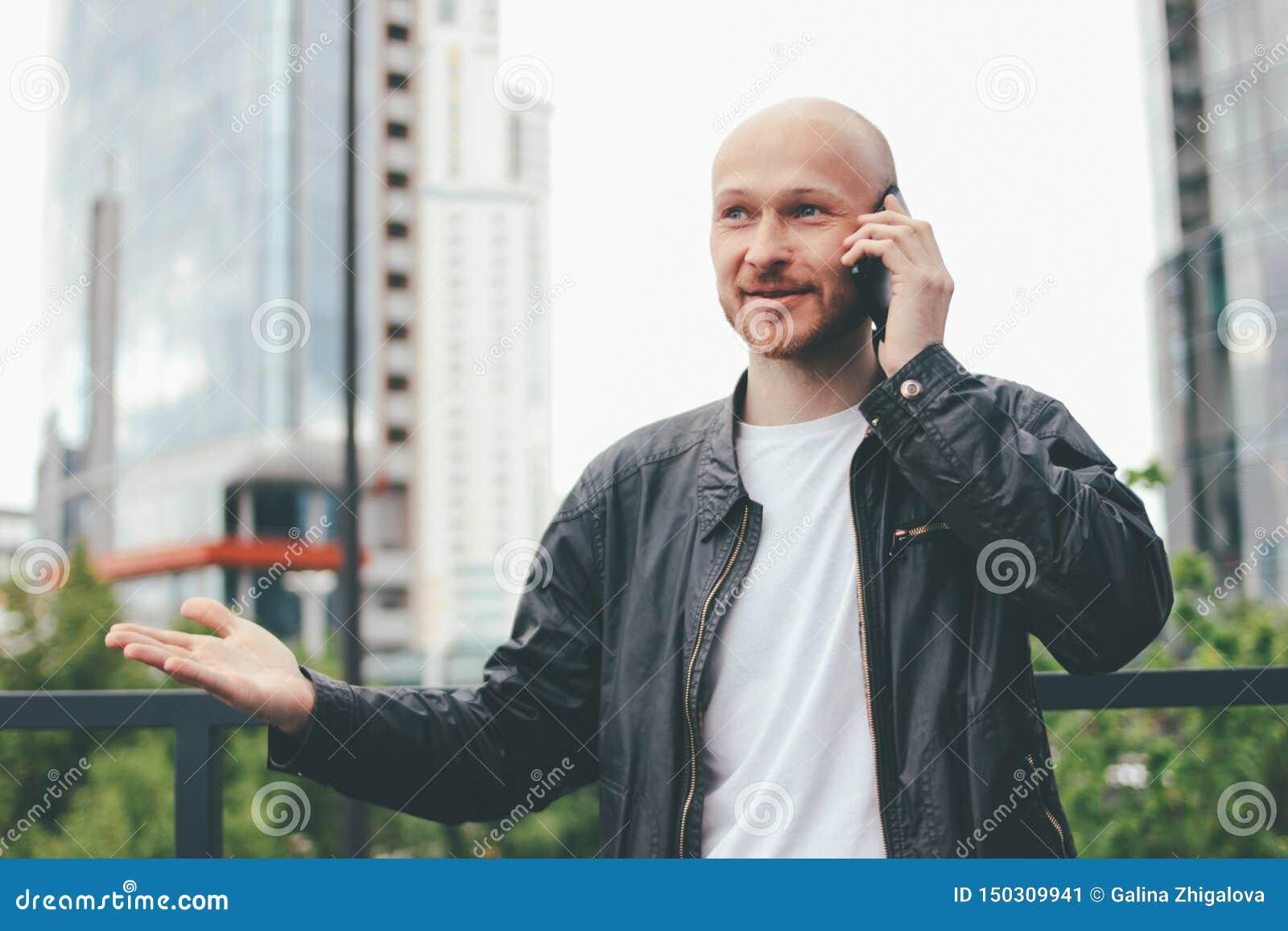 Ενήλικο ελκυστικό φαλακρό γενειοφόρο άτομο που μιλά από κινητό στην οδό πόλεων