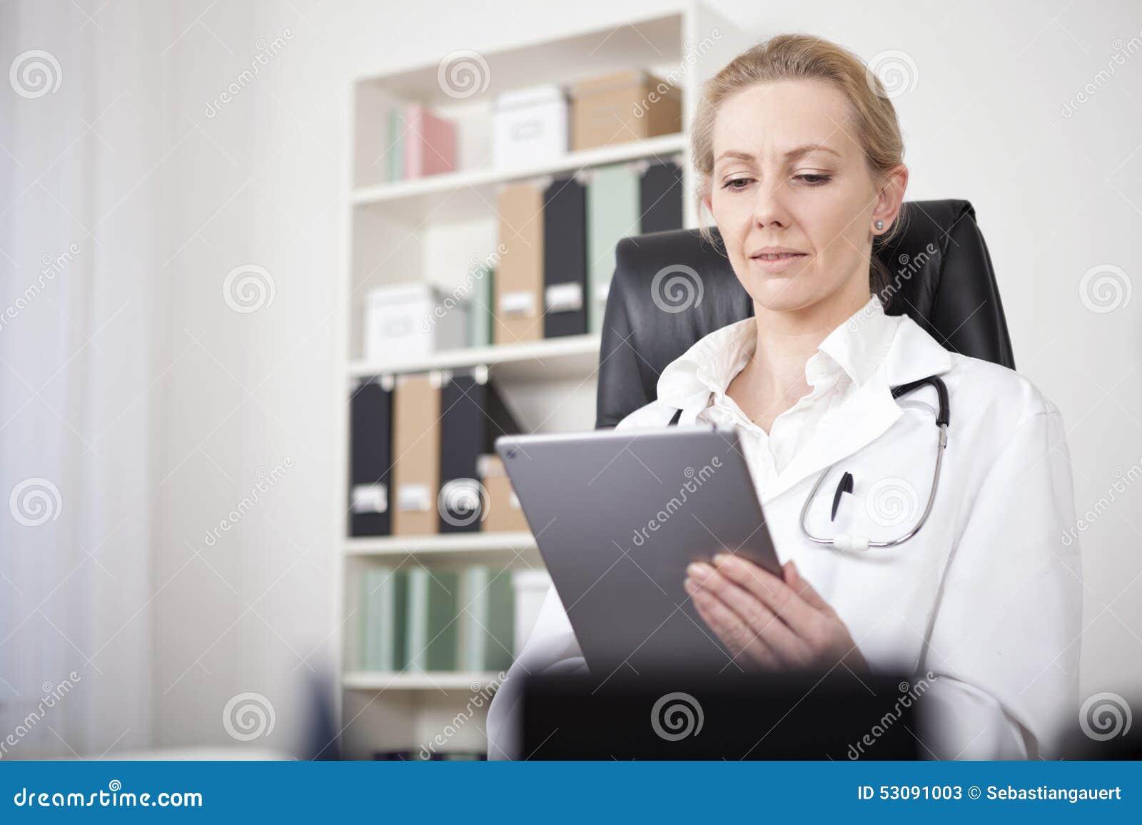 Ενήλικος θηλυκός γιατρός που εξετάζει την οθόνη ταμπλετών της