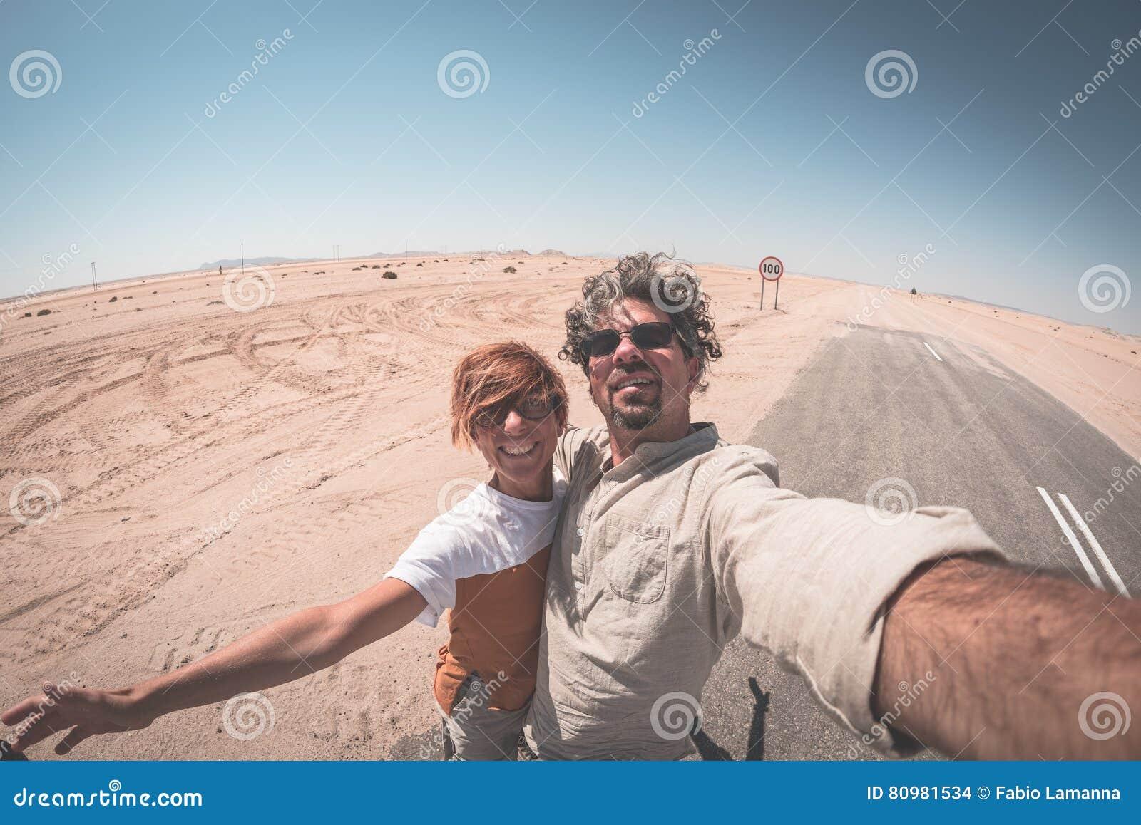 Ενήλικο ζεύγος που παίρνει selfie στο δρόμο στην έρημο Namib, εθνικό πάρκο Namib Naukluft, κύριος προορισμός ταξιδιού στη Ναμίμπι