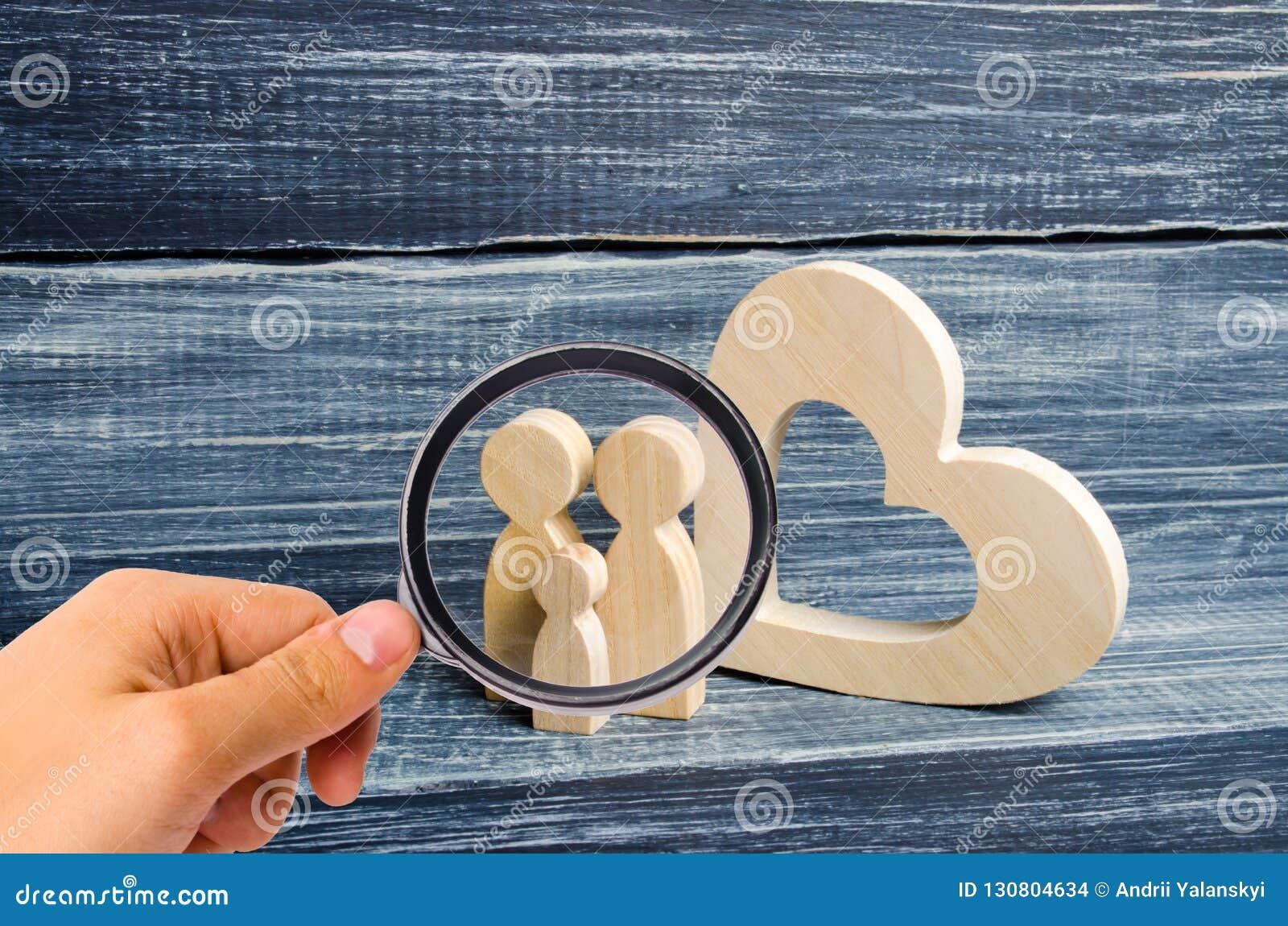 Ενίσχυση - το γυαλί εξετάζει τη νέα οικογένεια με ένα παιδί στέκεται κοντά σε μια ξύλινη καρδιά Αγάπη και πίστη,