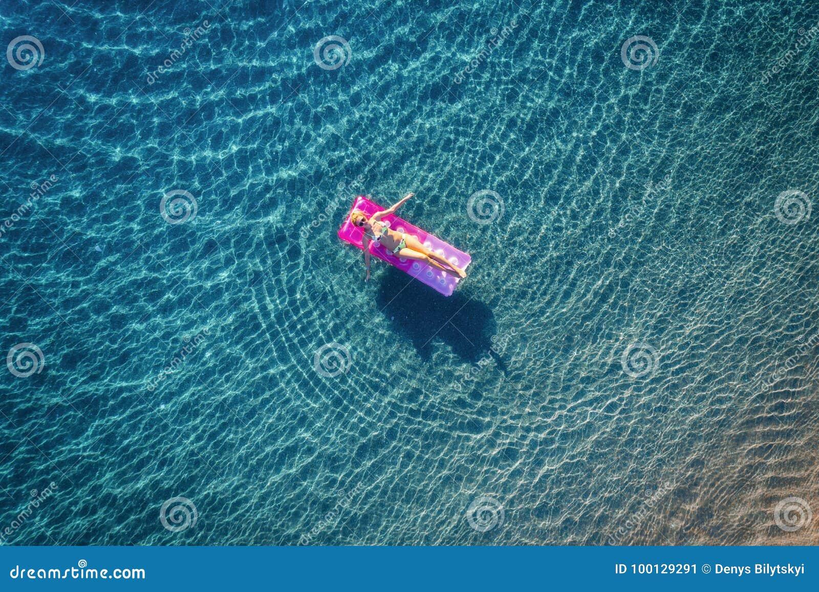 Εναέρια άποψη της νέας κολύμβησης γυναικών στο ρόδινο διογκώσιμο mattr