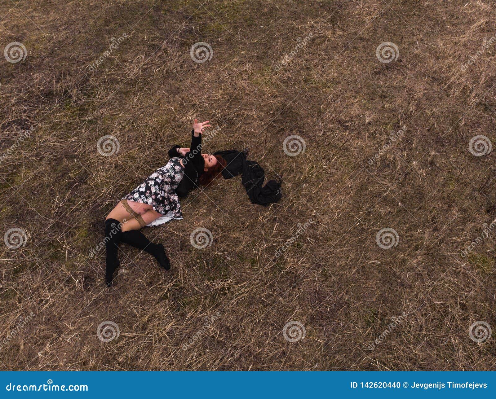 Εναέρια τοπ άποψη κηφήνων ενός κοριτσιού που βρίσκεται σε έναν τομέα που χαλαρώνει και που χορεύει Φθορά ενός φορέματος με τις γυ