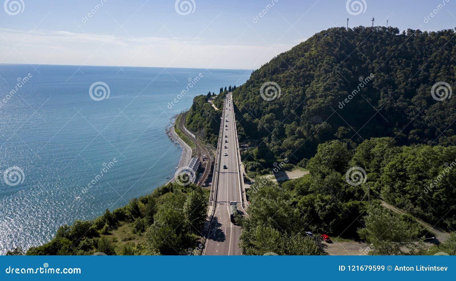 Εναέρια φωτογραφία αποθεμάτων της οδήγησης αυτοκινήτων κατά μήκος του άνεμος δρόμου περασμάτων βουνών μέσω του δάσους στο Sochi,