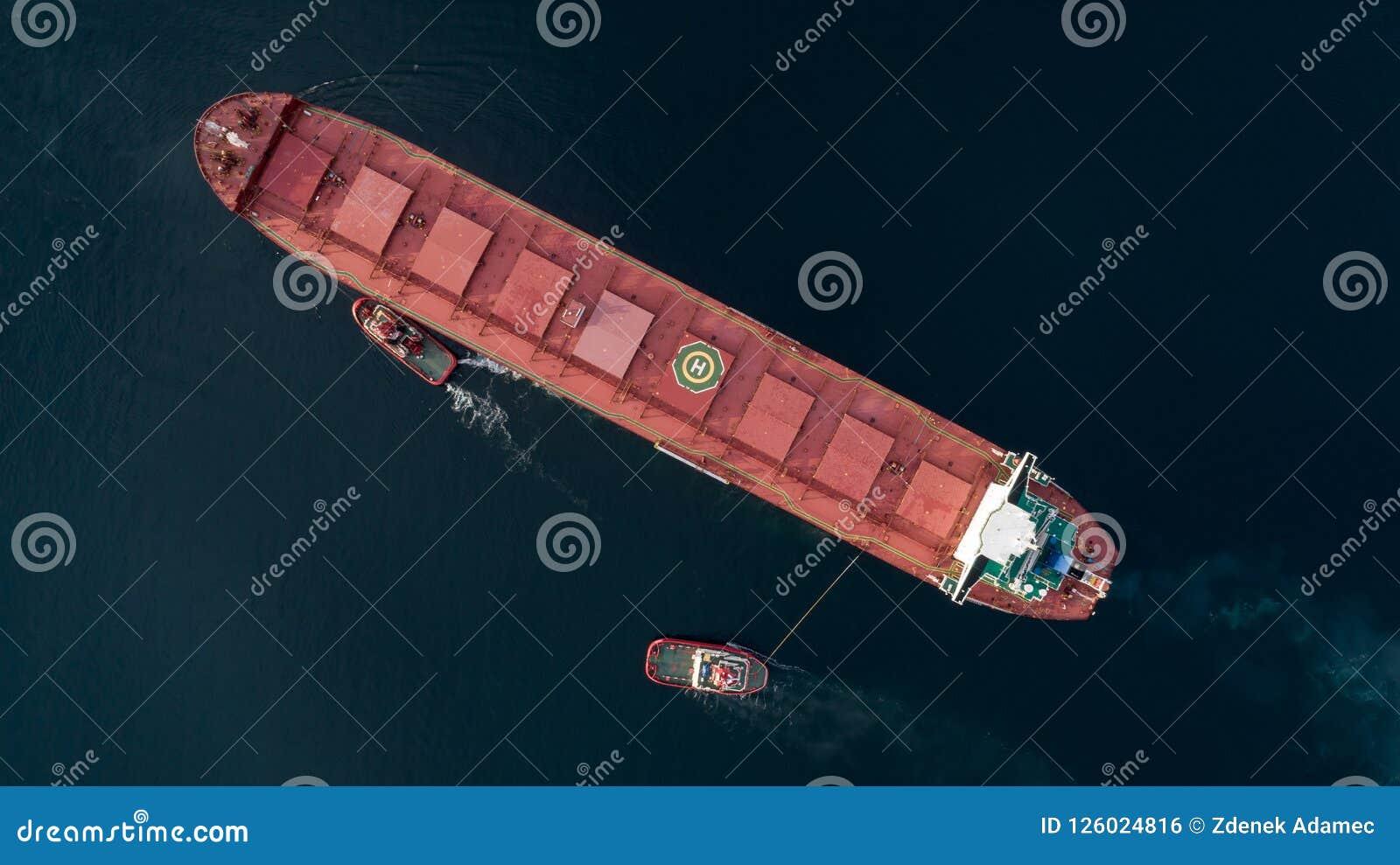 Εναέριος πυροβολισμός ενός πλησιάζοντας λιμένα φορτηγών πλοίων με τη βοήθεια της ρυμούλκησης του σκάφους
