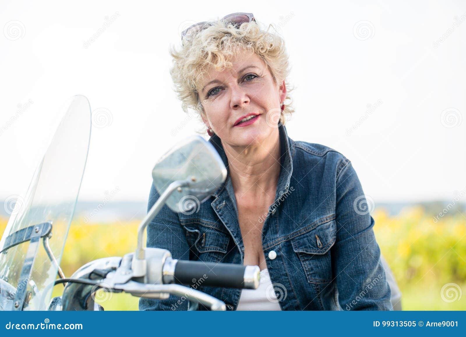 Ενεργός ανώτερη γυναίκα που φορά ένα μπλε σακάκι τζιν καθμένος επάνω