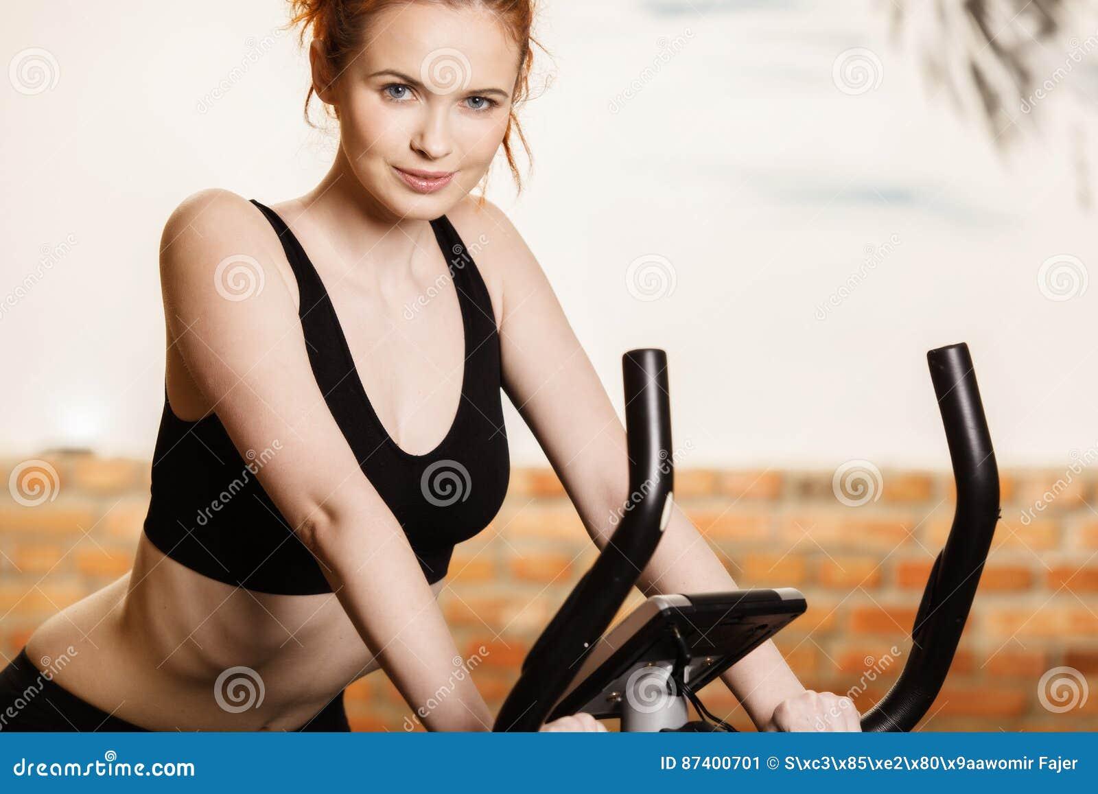 Ενεργός νέα γυναίκα που κάνει την άσκηση στο ποδήλατο στο σπίτι