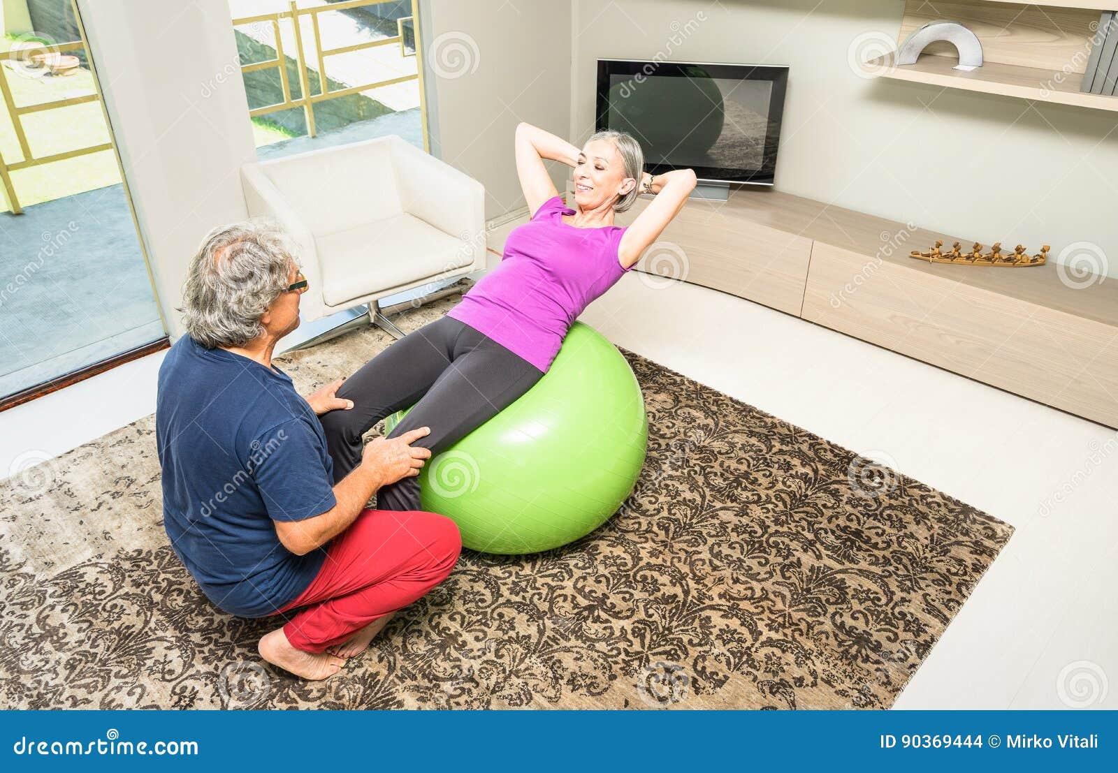 Ενεργό ηλικιωμένο ζεύγος στην κατάρτιση ικανότητας με την ελβετική σφαίρα στο σπίτι