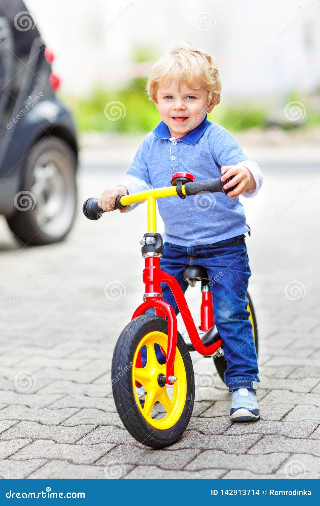 Ενεργό ξανθό αγόρι παιδιών στα ζωηρόχρωμα ενδύματα που οδηγούν την ισορροπία και το ποδήλατο του αρχαρίου ή ποδήλατο στον εσωτερι