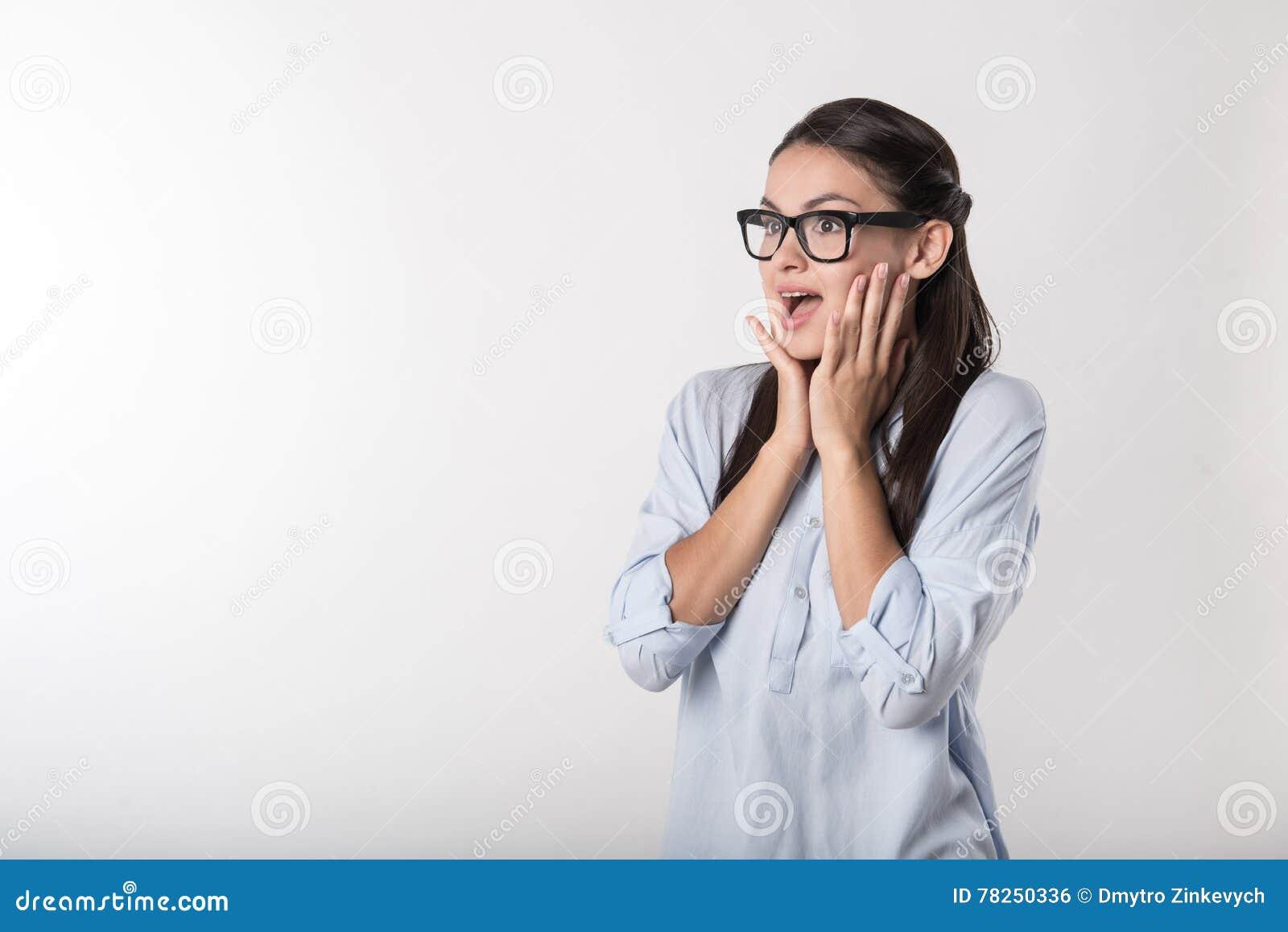 Ενθουσιασμένη έκπληκτη γυναίκα που στέκεται στο άσπρο κλίμα