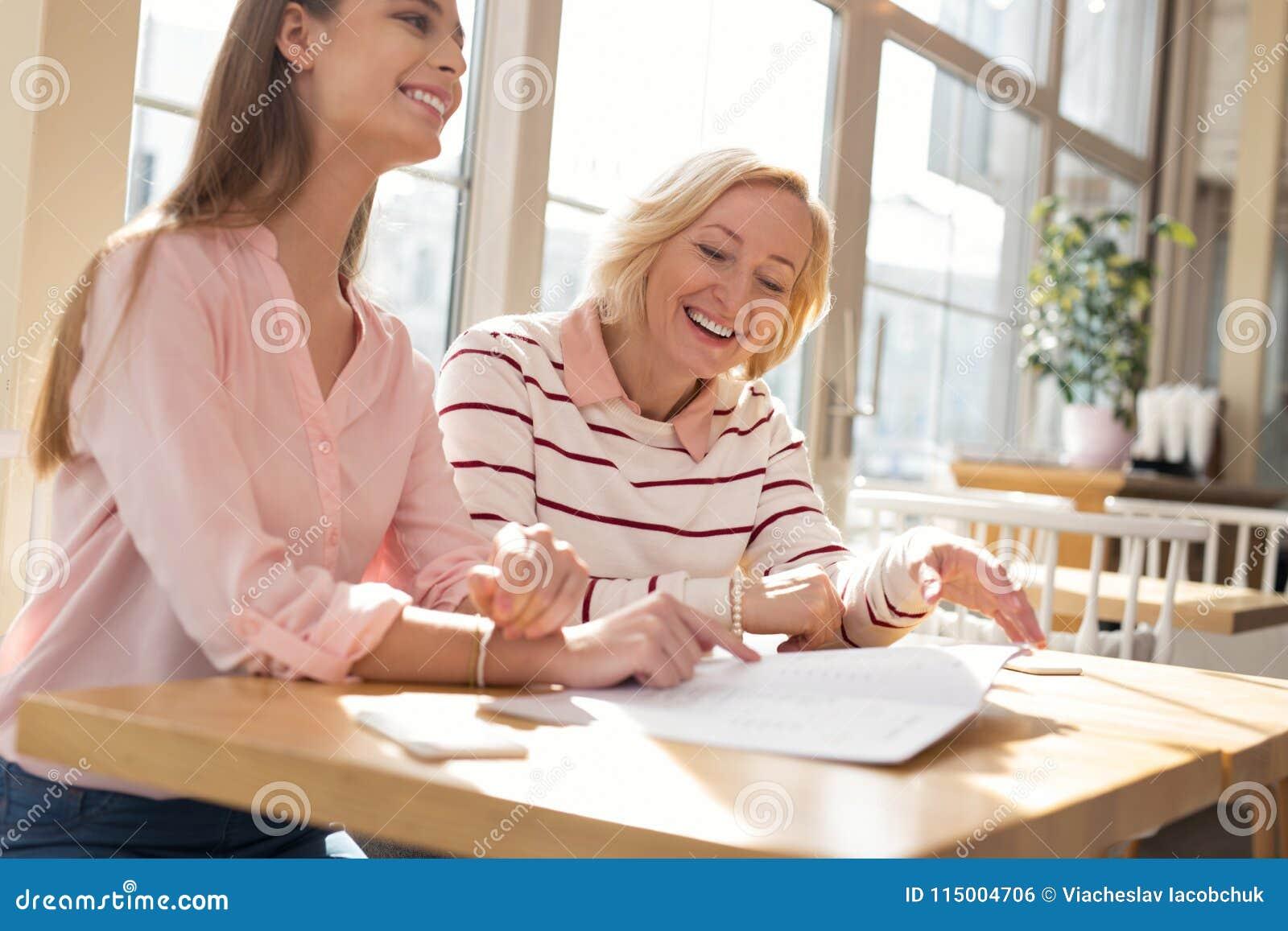 Ενθουσιώδης γιαγιά που συζητά τη οικογενειακή επιχείρηση με την εγγονή της