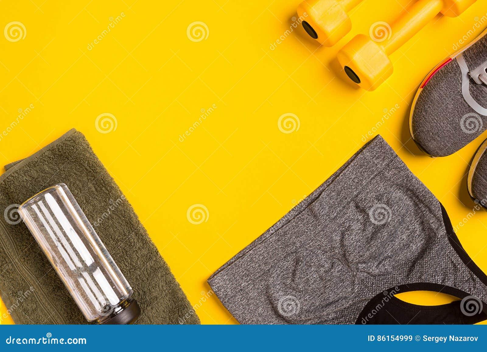 Εξαρτήματα ικανότητας σε ένα κίτρινο υπόβαθρο Πάνινα παπούτσια, μπουκάλι νερό, έξυπνη, κορυφή πετσετών και αθλητισμού