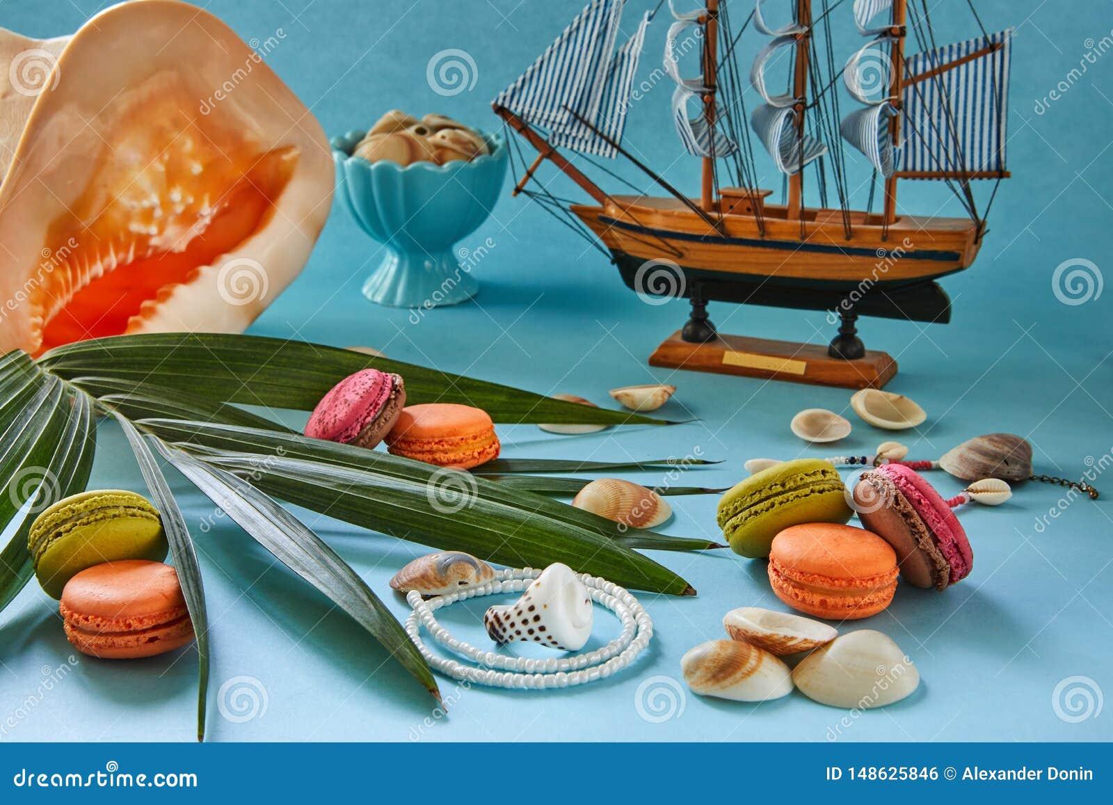 Εξαρτήματα παραλιών, φρέσκα νόστιμα φρούτα και macaron σε ένα μπλε υπόβαθρο